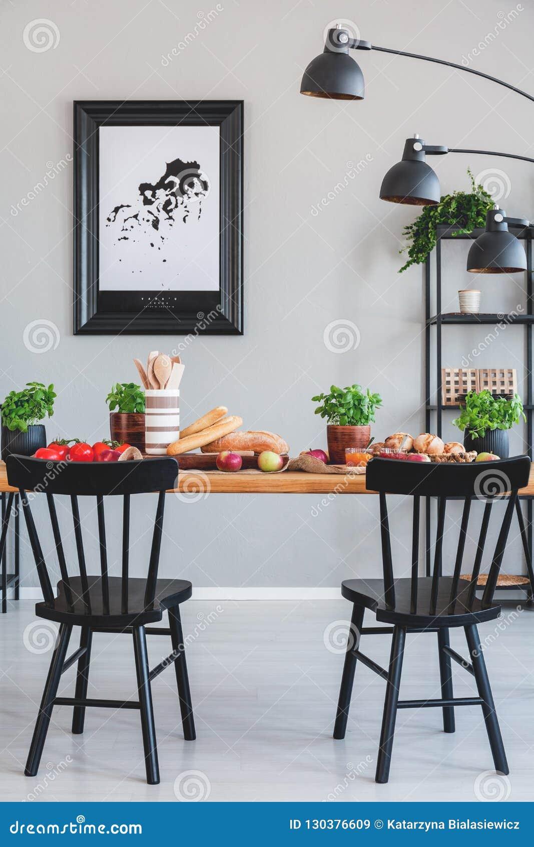 Affisch på den gråa väggen i industriell matsal som är inre med svarta stolar och lampan på tabellen