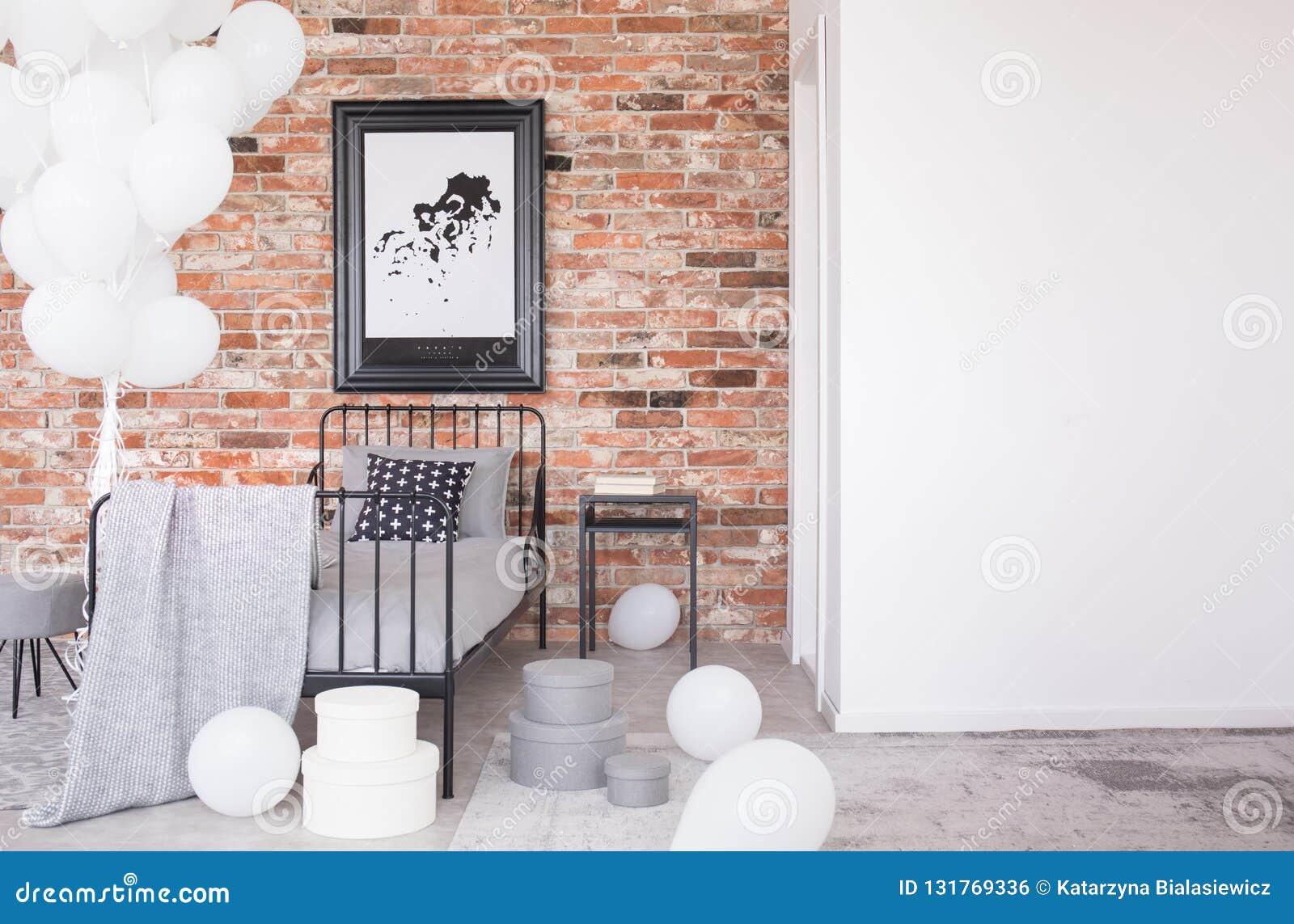 Affisch på väggen för röd tegelsten ovanför säng i inre med kopieringsutrymme och ballonger Verkligt foto