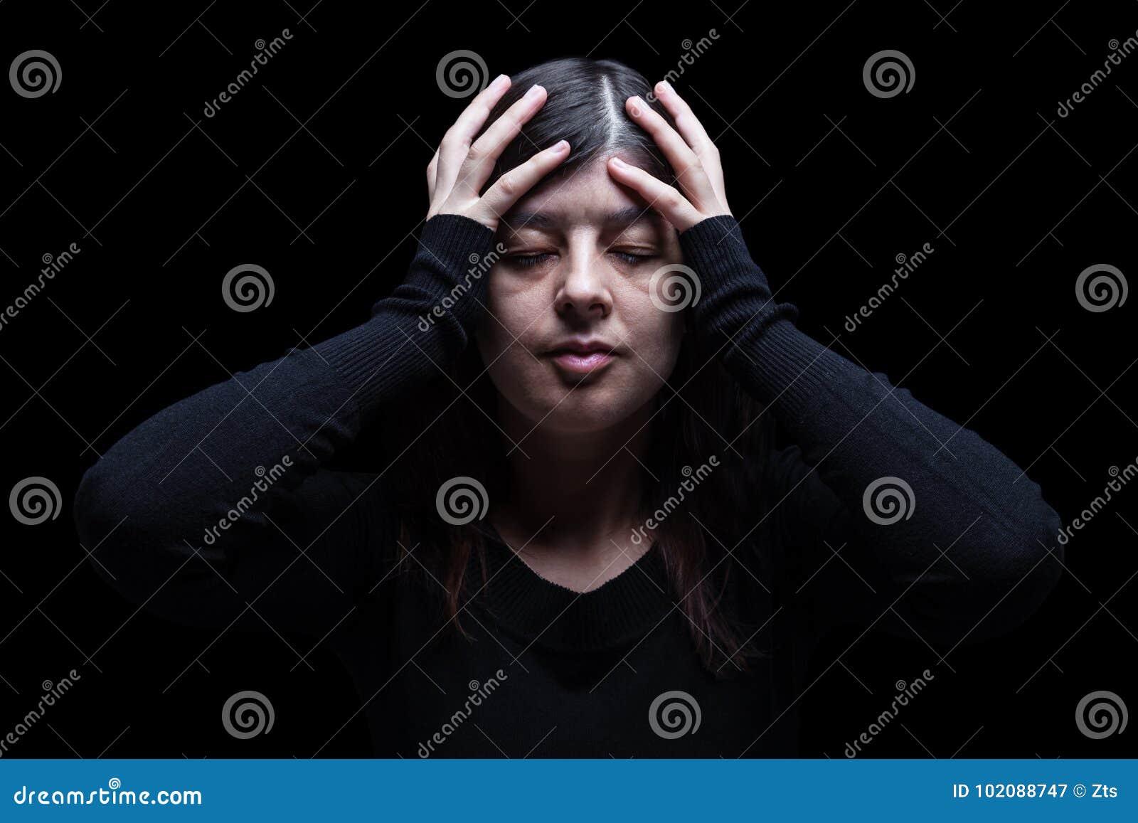 Afflitto, donna tenenti la testa con le mani, su un fondo nero o scuro