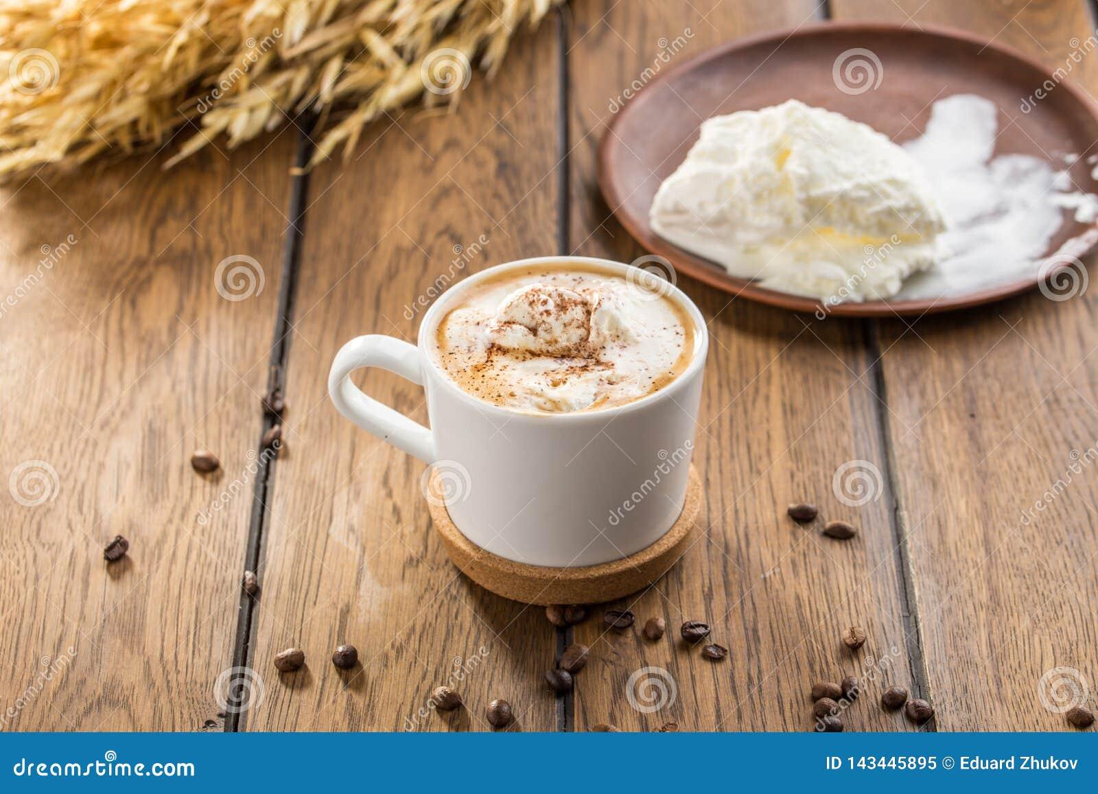 Affogato-Kaffee mit Eiscreme in den Glasschalen- und Weizenspitzen auf Holztisch