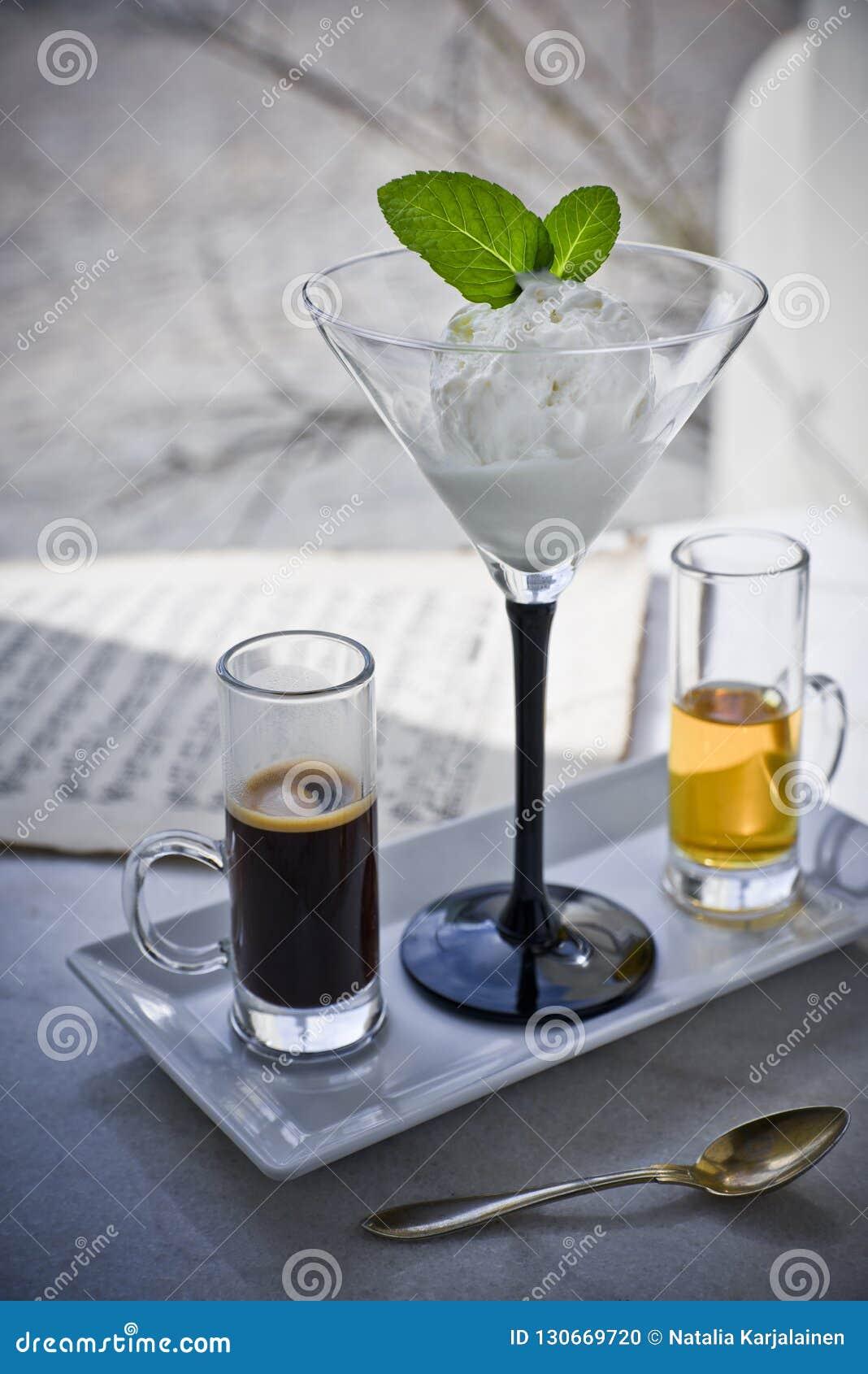 Affogato med med glass, jordgubbar, mintkaramellsidor, espresso och likör på marmorerar tabellen