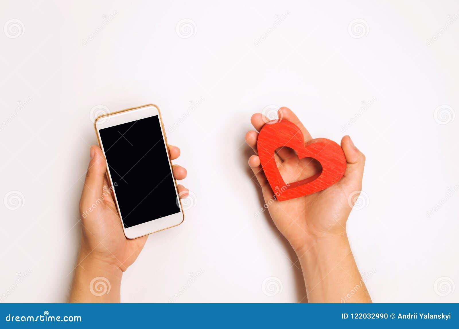 Afhankelijkheid van sociale netwerken telefoonsmartphone en hart in handen het dateren online, het flirten, bericht en het roepen