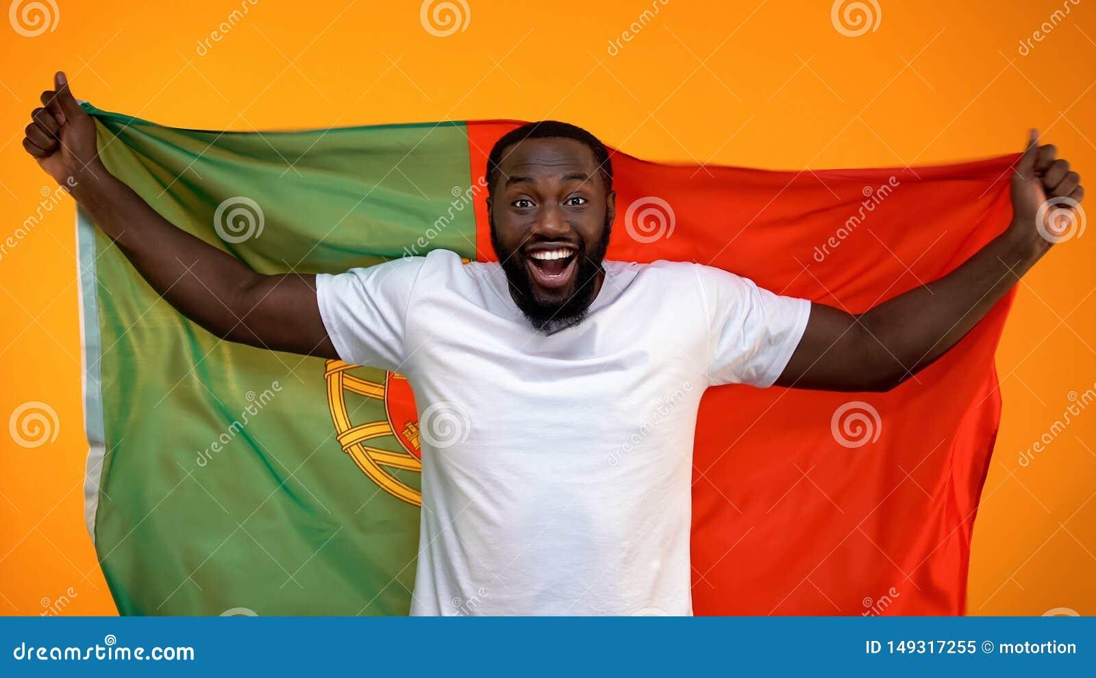 Aficionado desportivo afro-americano surpreendido que guarda a bandeira portuguesa, cheering para a vit?ria