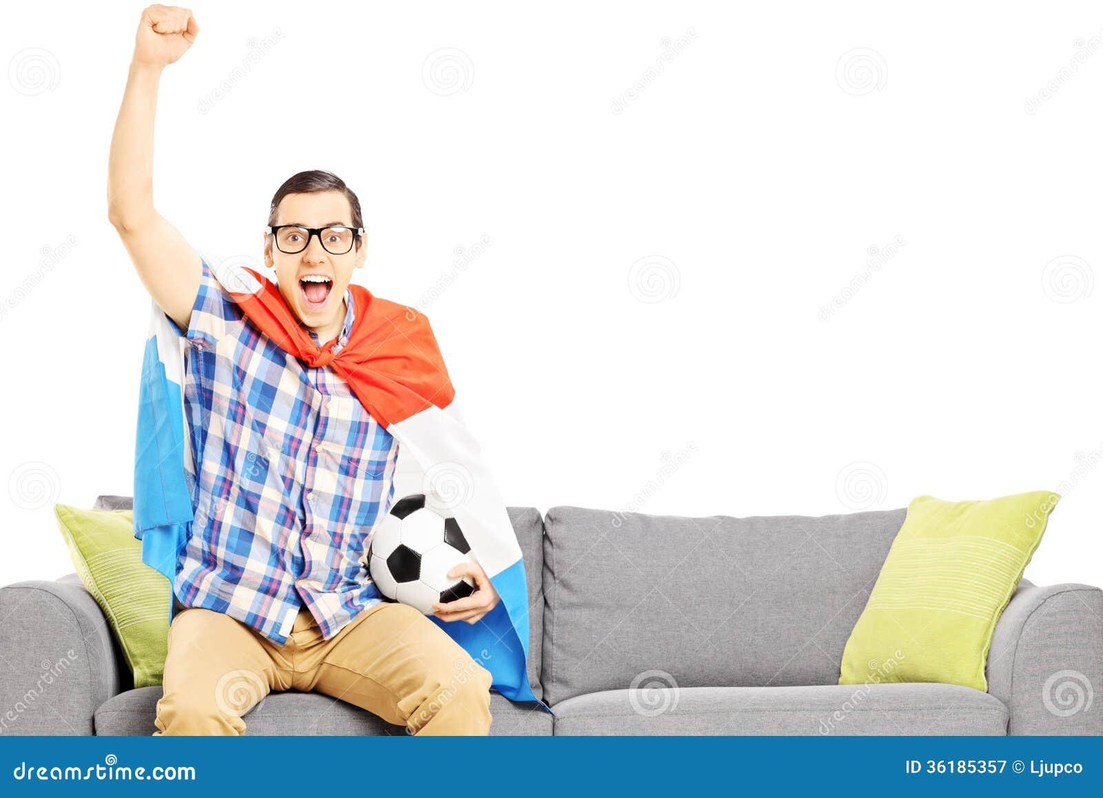 Aficionado desportivo masculino alegre com esporte de observação da bola e da bandeira de futebol