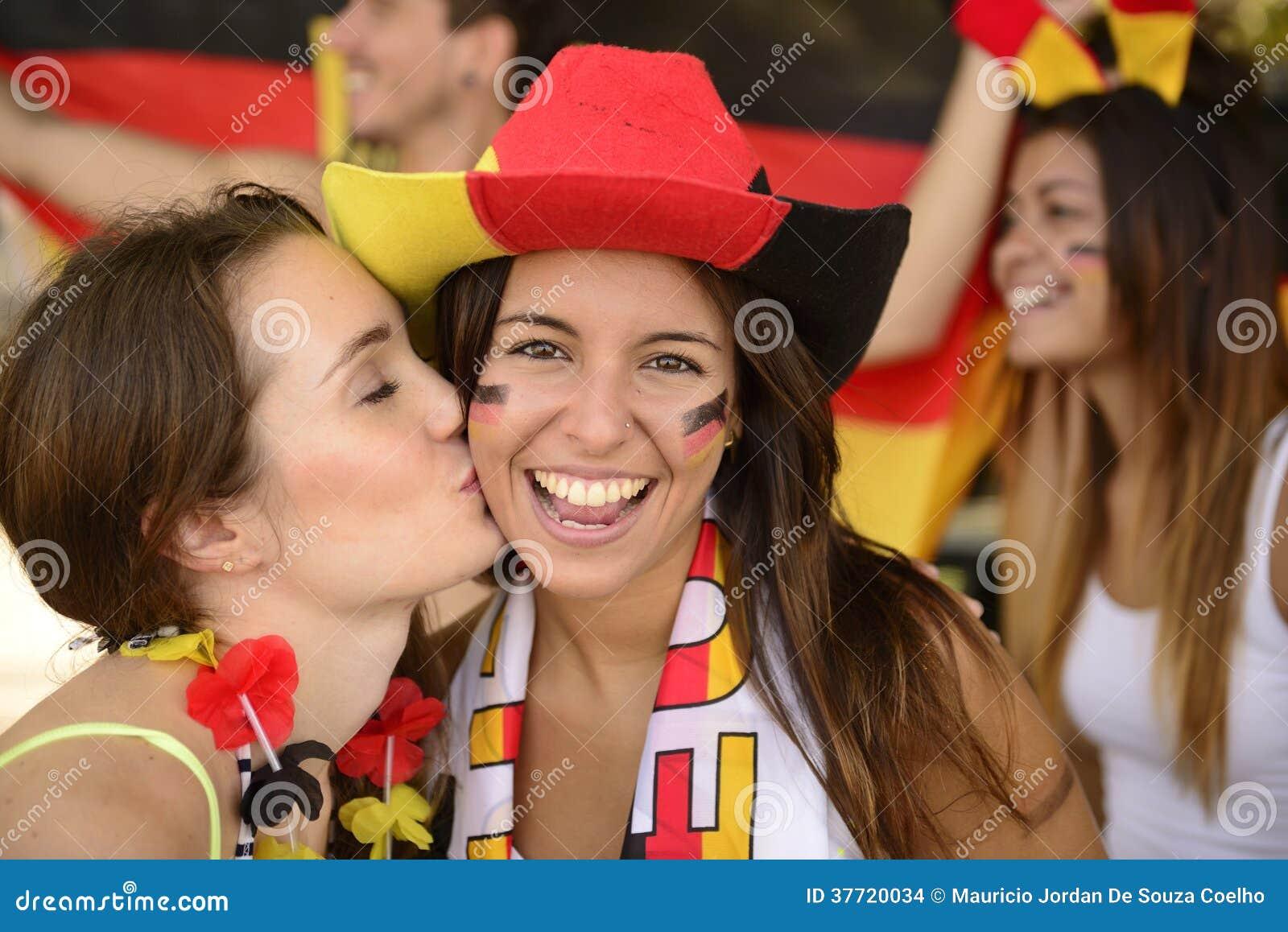 Aficionados deportivos alemanes del fútbol que besan la celebración.