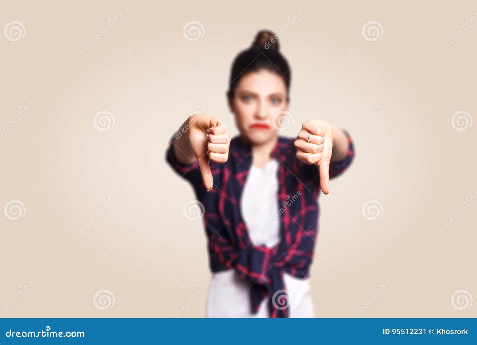 Afkeer Het jonge ongelukkige verstoorde meisje met toevallig stijl en broodjeshaar beduimelt onderaan haar vinger, op beige blind