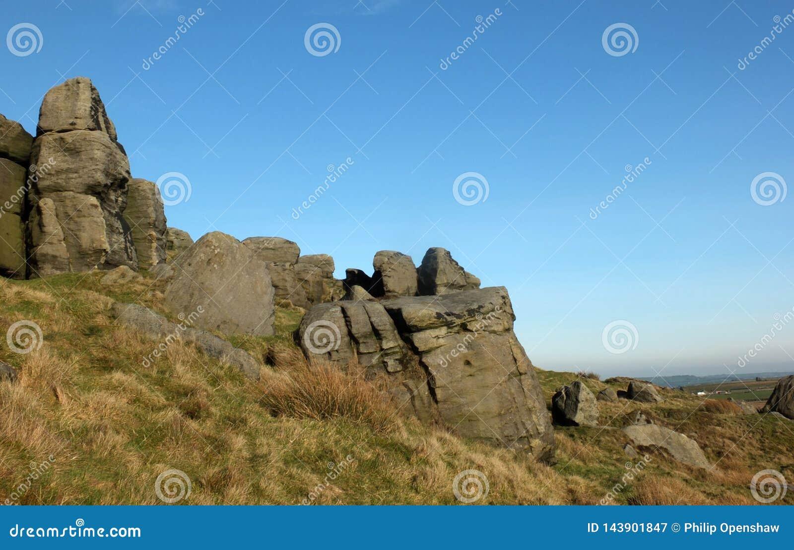 Afloramiento rugoso grande del gritstone en los bridestones una formaci?n de roca grande en West Yorkshire cerca del cielo azul d