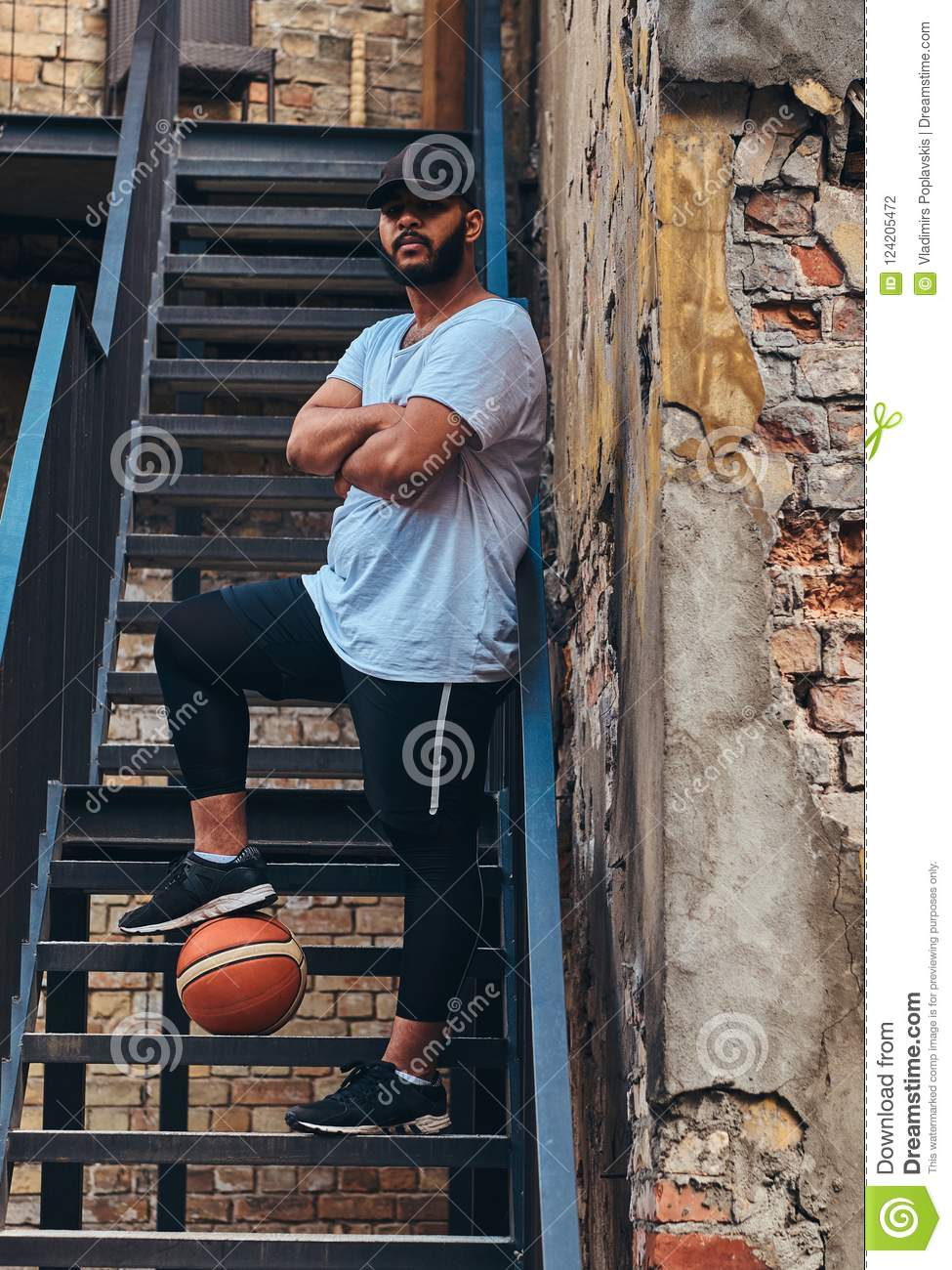 African-American bearded streetball player in cap dressed in a sportswear holds a basketball standing with crossed arms