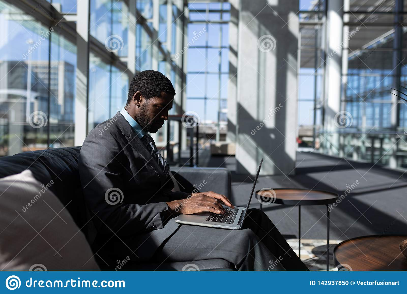 African-American businessman sitting on the sofa and using laptop in modern office