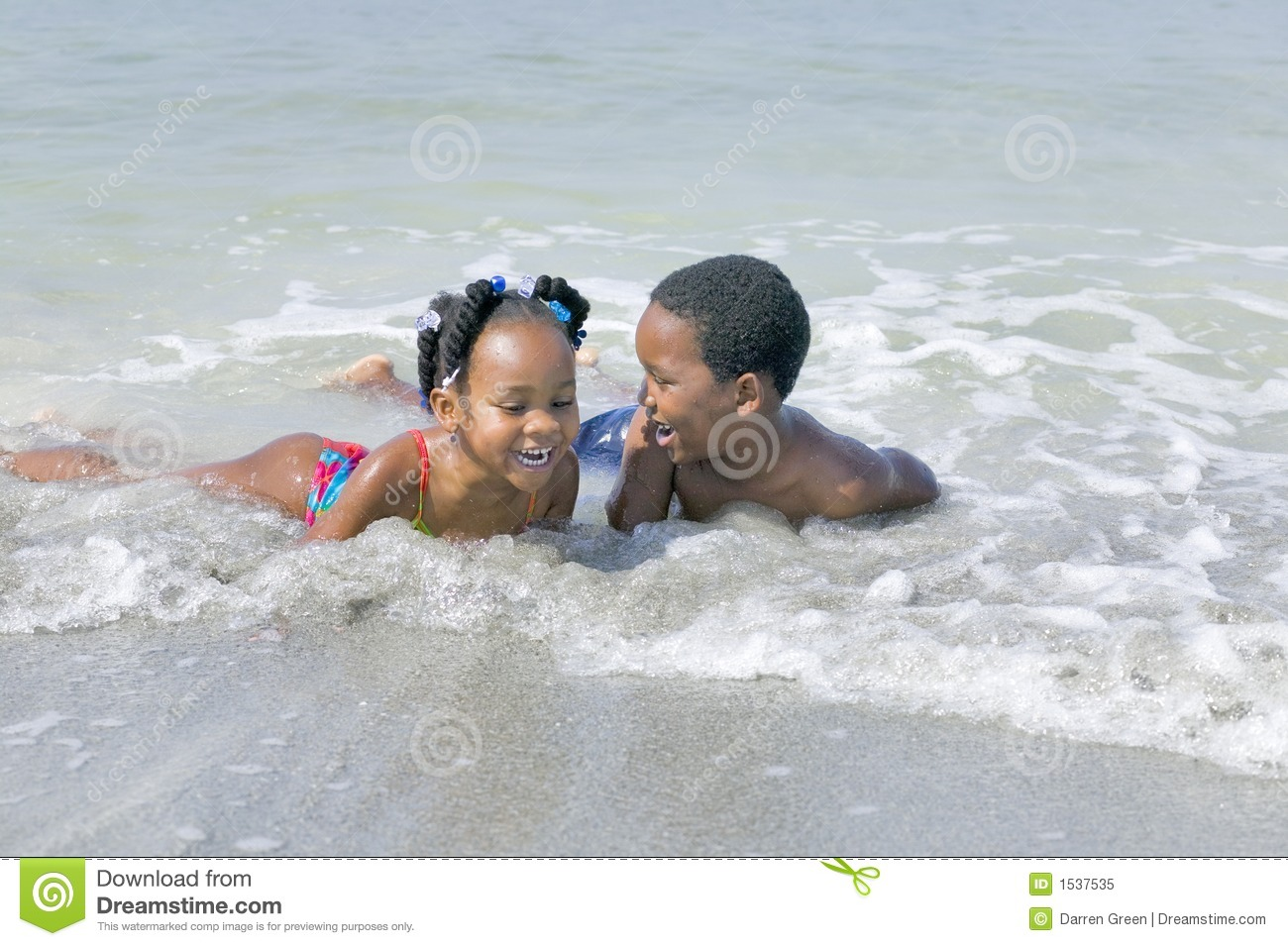 African American Children Playing At The Beach