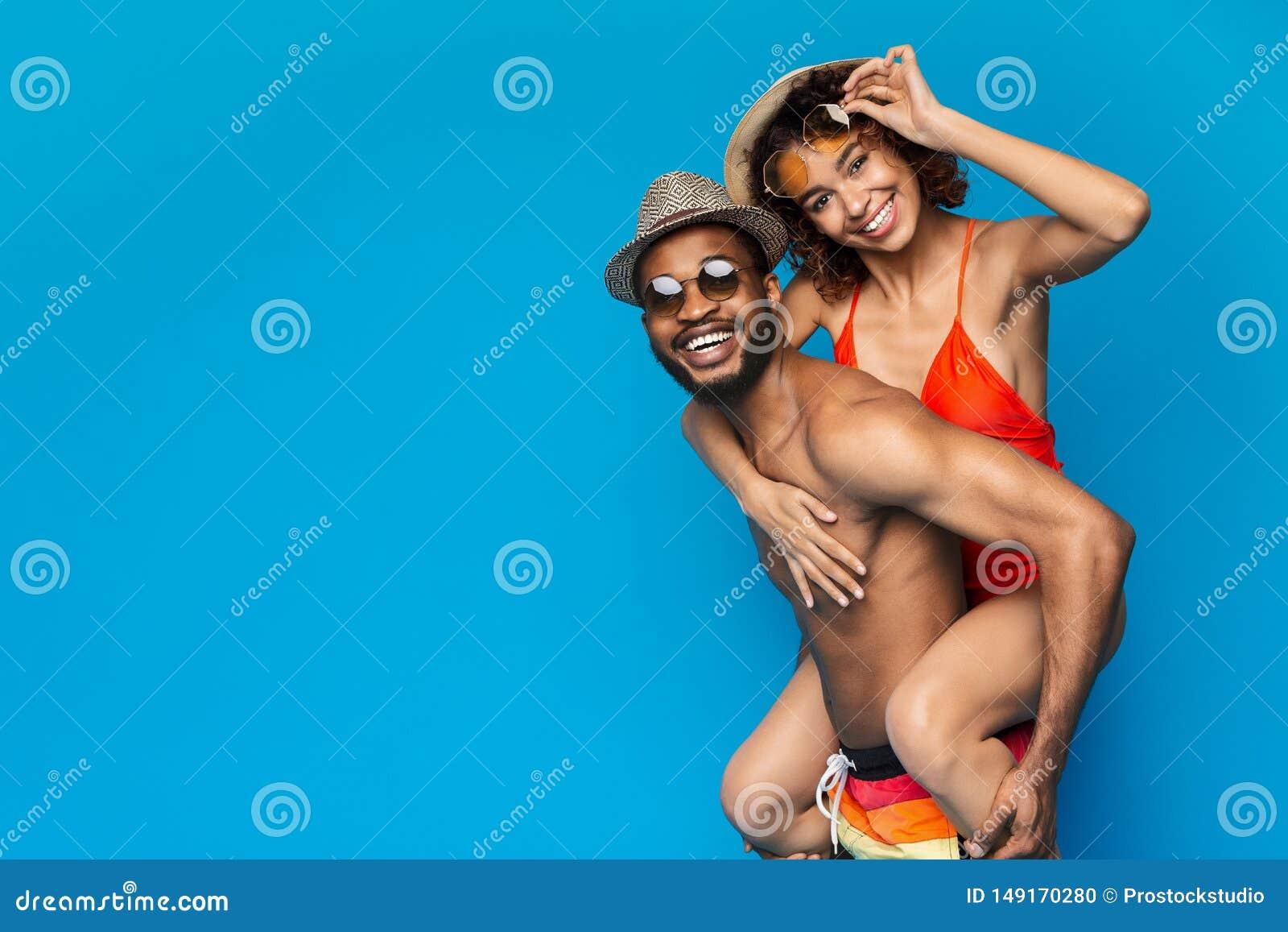African american couple fooling, man piggybacking his girlfriend