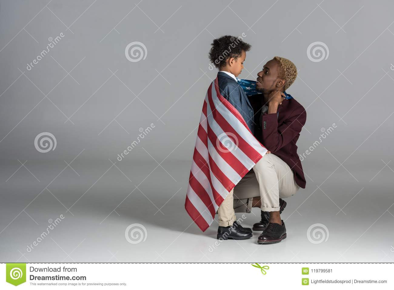 african american family wrapped in flag on grey