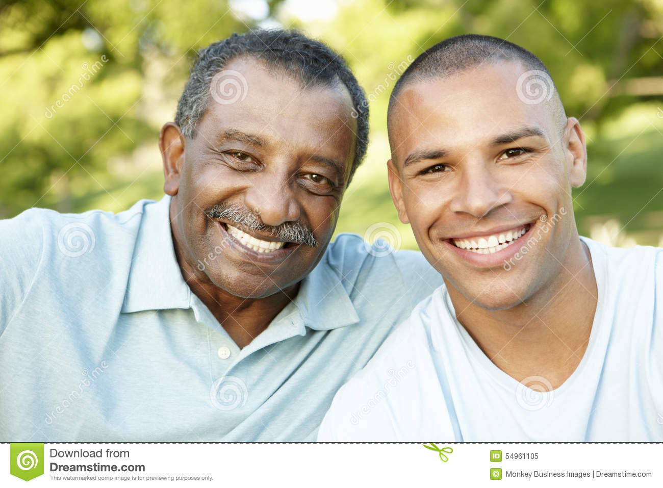 African American Father And Adult Son Relaxing In Park