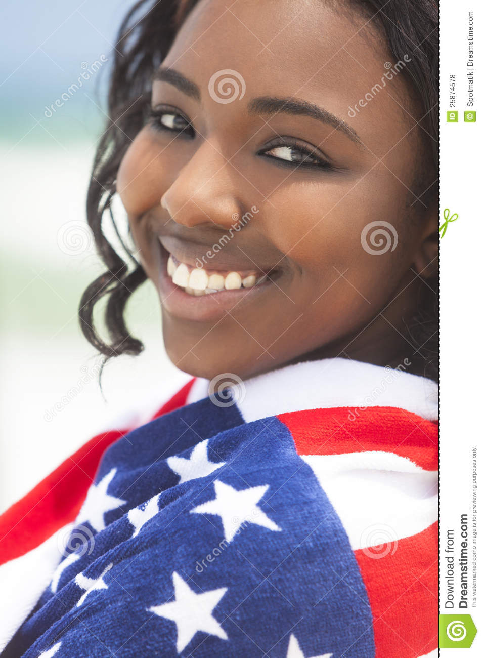 African American Girl in American Flag on Beach