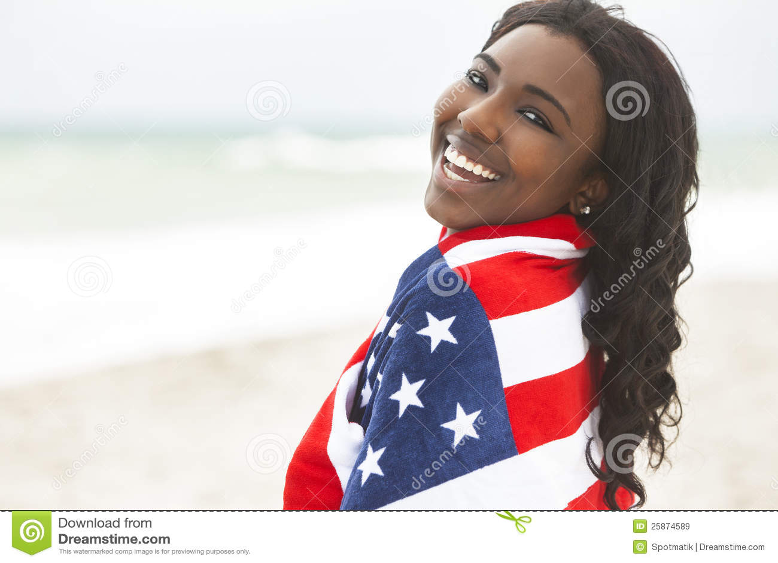African American Girl in American Flag on Beach