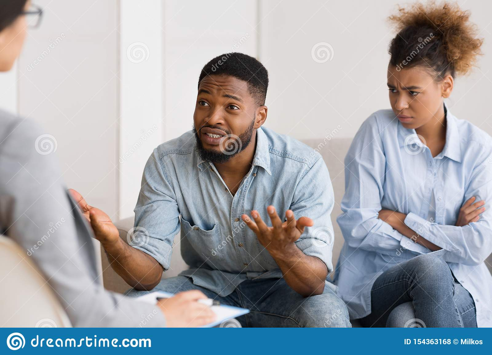 African American Husband Talking To Psychologist Sitting Next To Wife