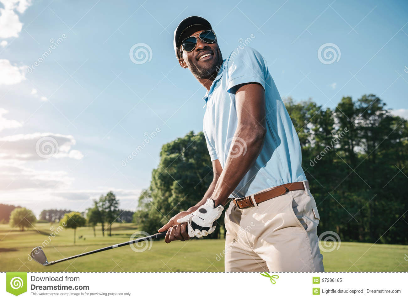 9093e70124d African american man in cap and sunglasses holding club and playing golf