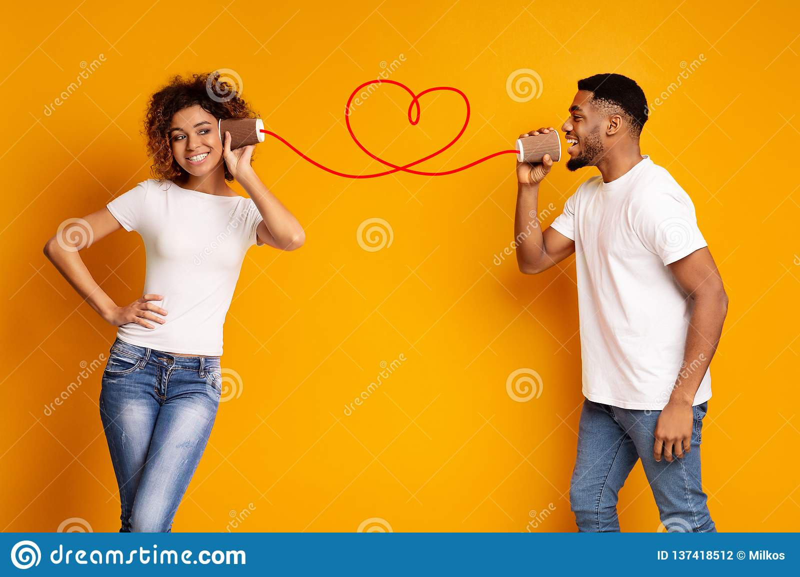 e7e6aa7e02 Young Black Couple With Can Phone On Orange Background Stock Photo ...
