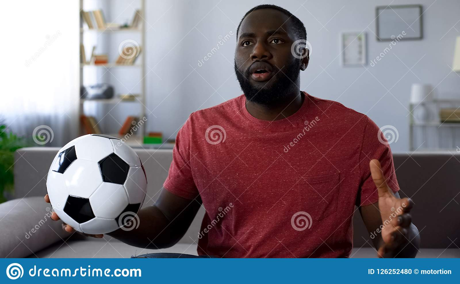 African-american man watching football game at home, unhappy with match score