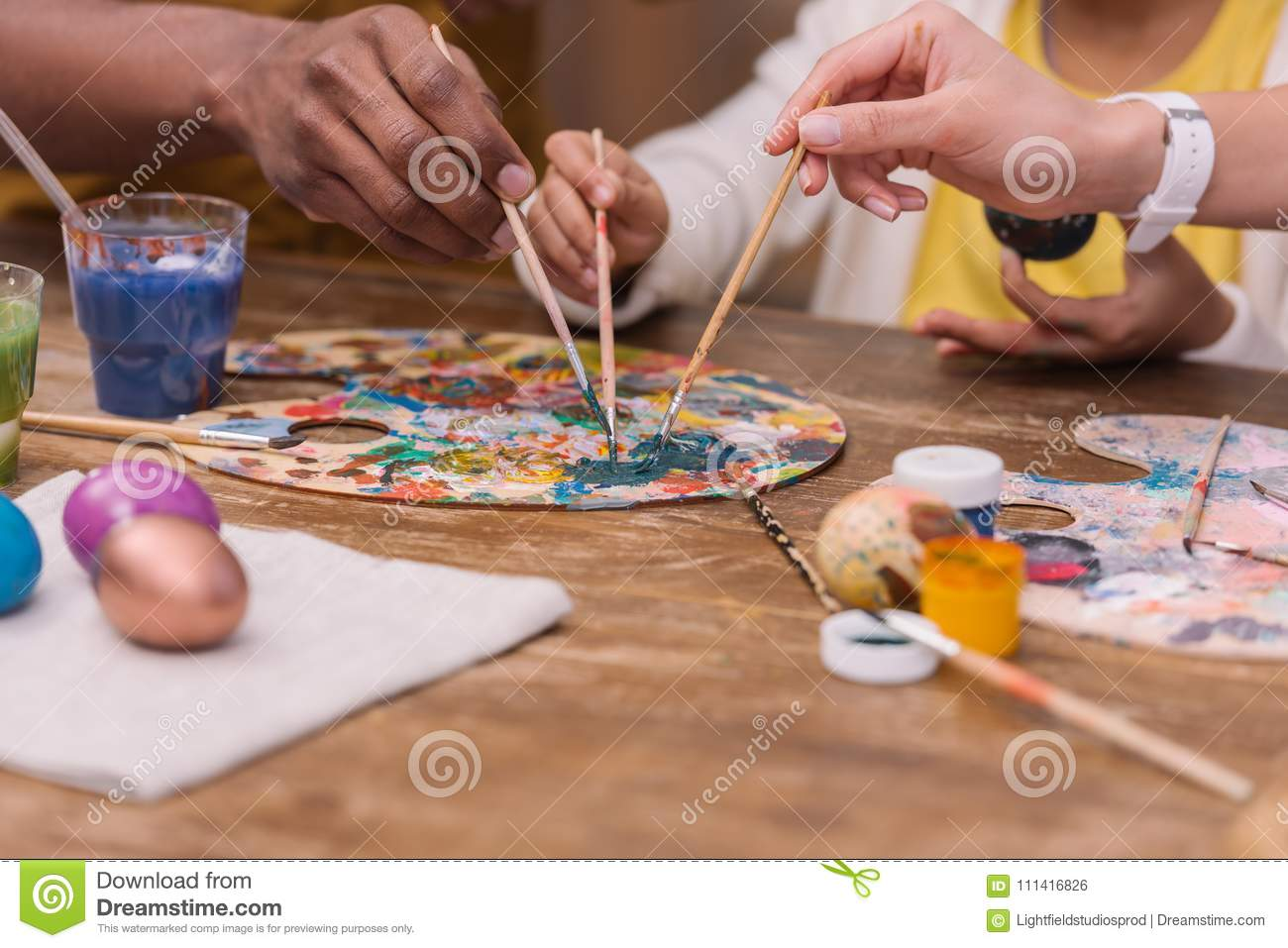 African american parents and daughter putting paint brushes on palette, easter concept