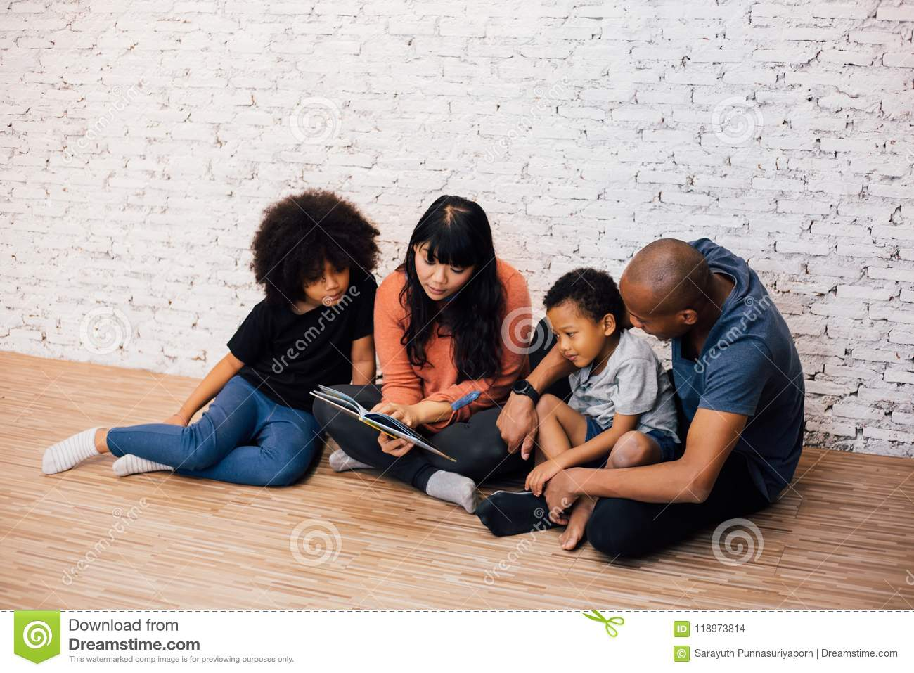 African American parents reading a fairy tale fable story for kids at home. Happy family sitting on the floor indoors.