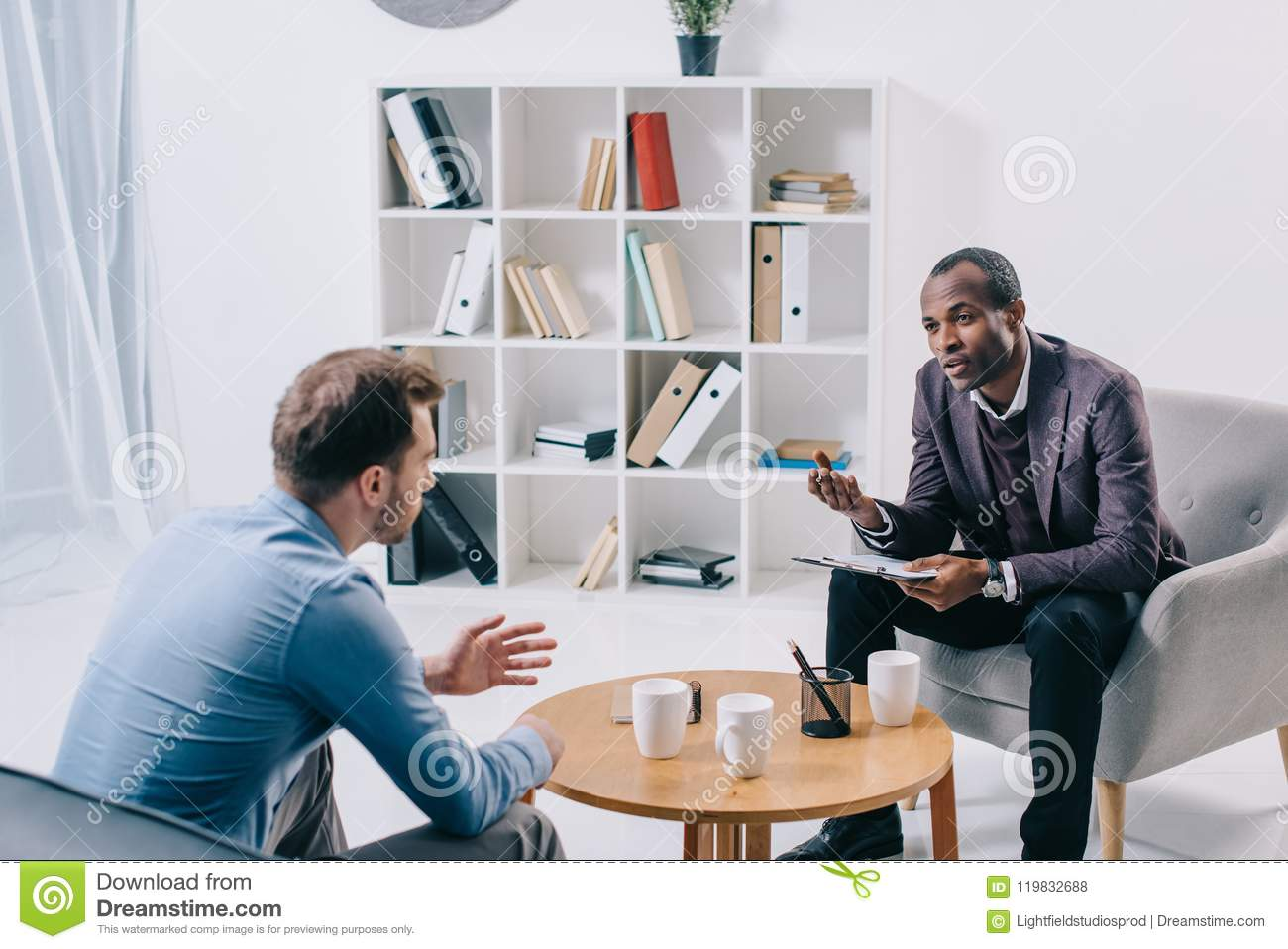 African american psychiatrist talking to young male