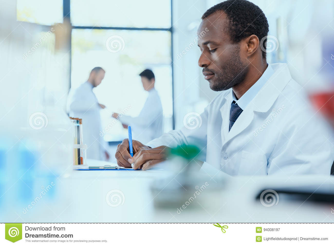 African American Scientist In White Coat Taking Notes While ...