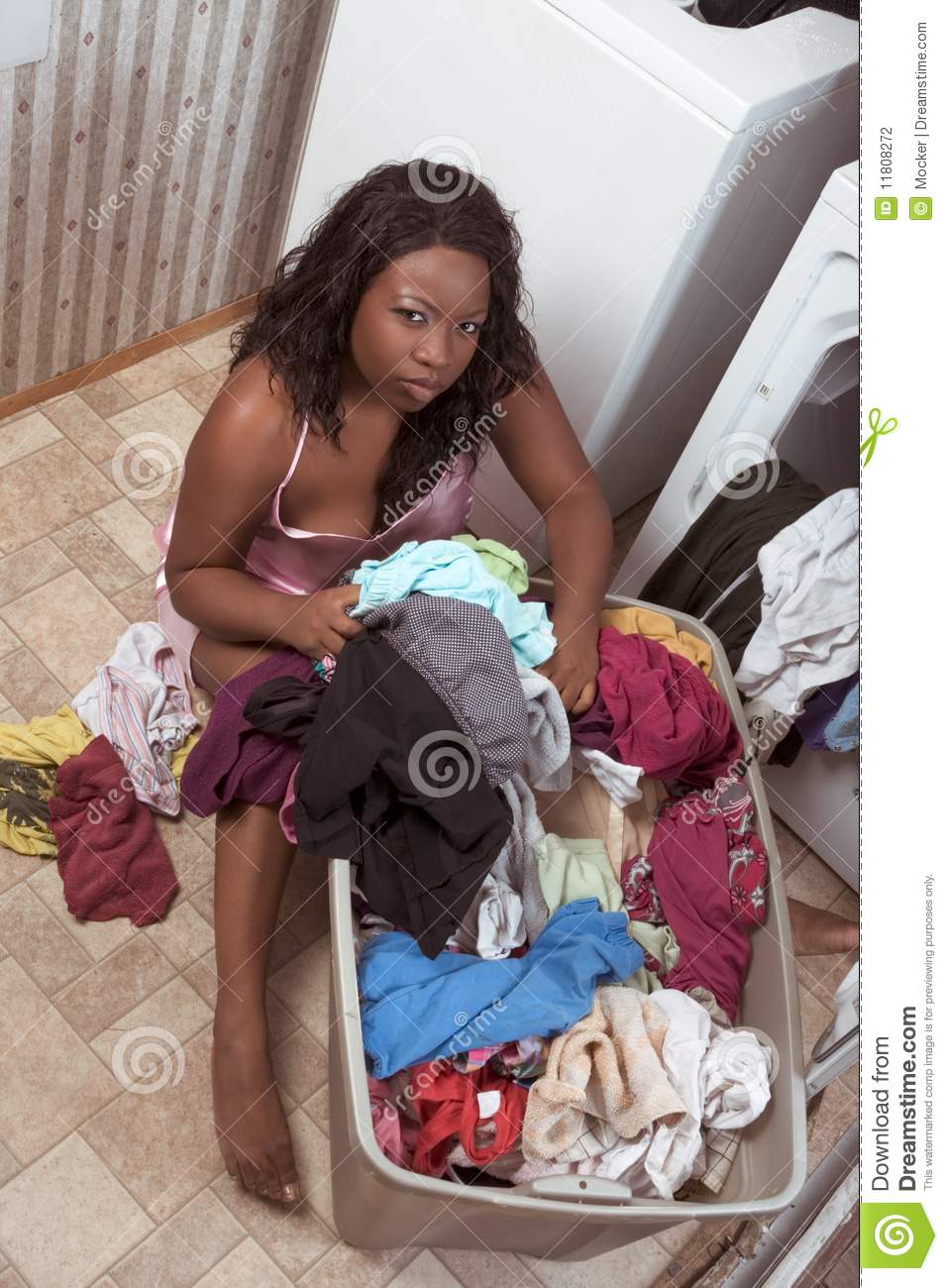 African American Woman By Basket Of Dirty Laundry Stock