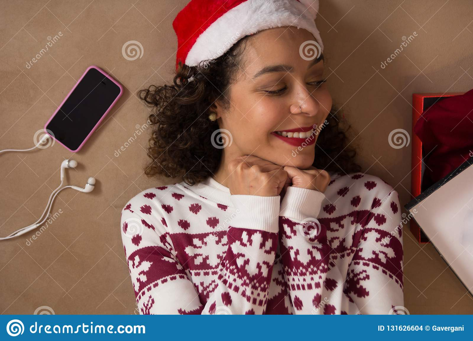 African American woman wearing Santa hat and Christmas sweater lying down and looking at gift box