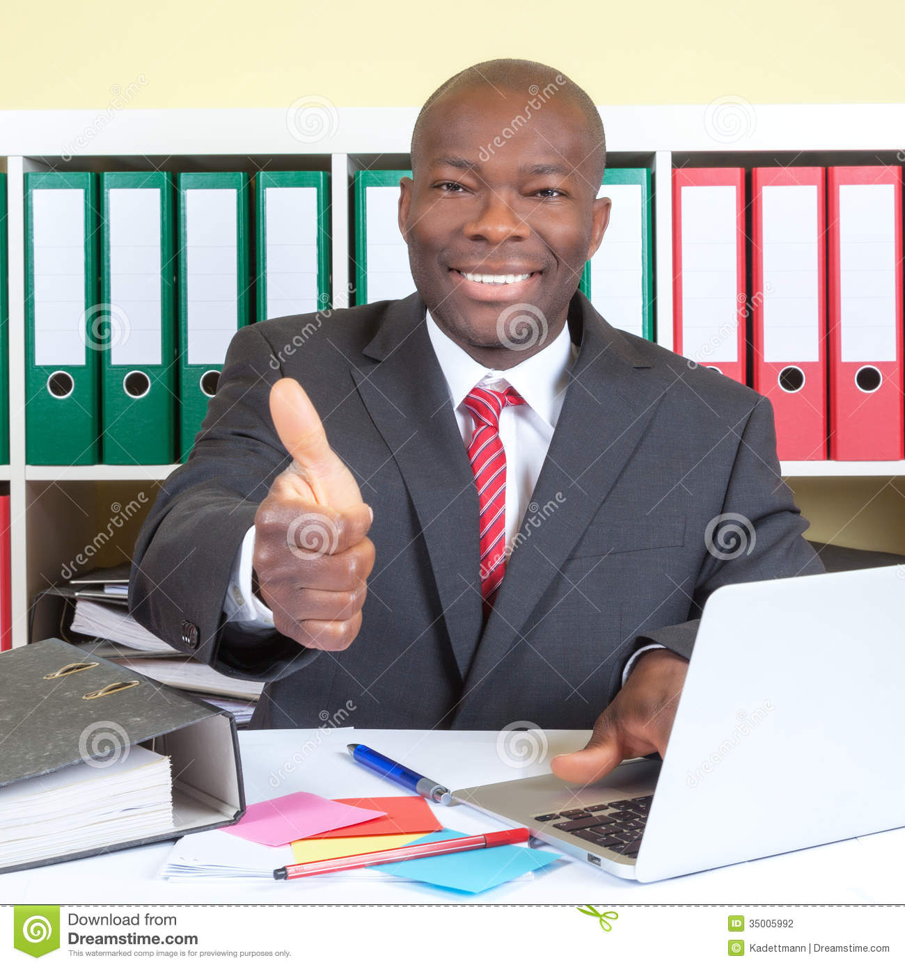 African businessman showing thumb up at his office