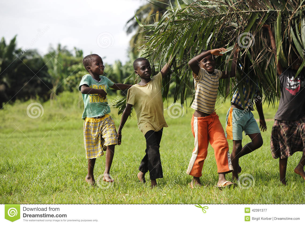 African kids help with carring palm leaves