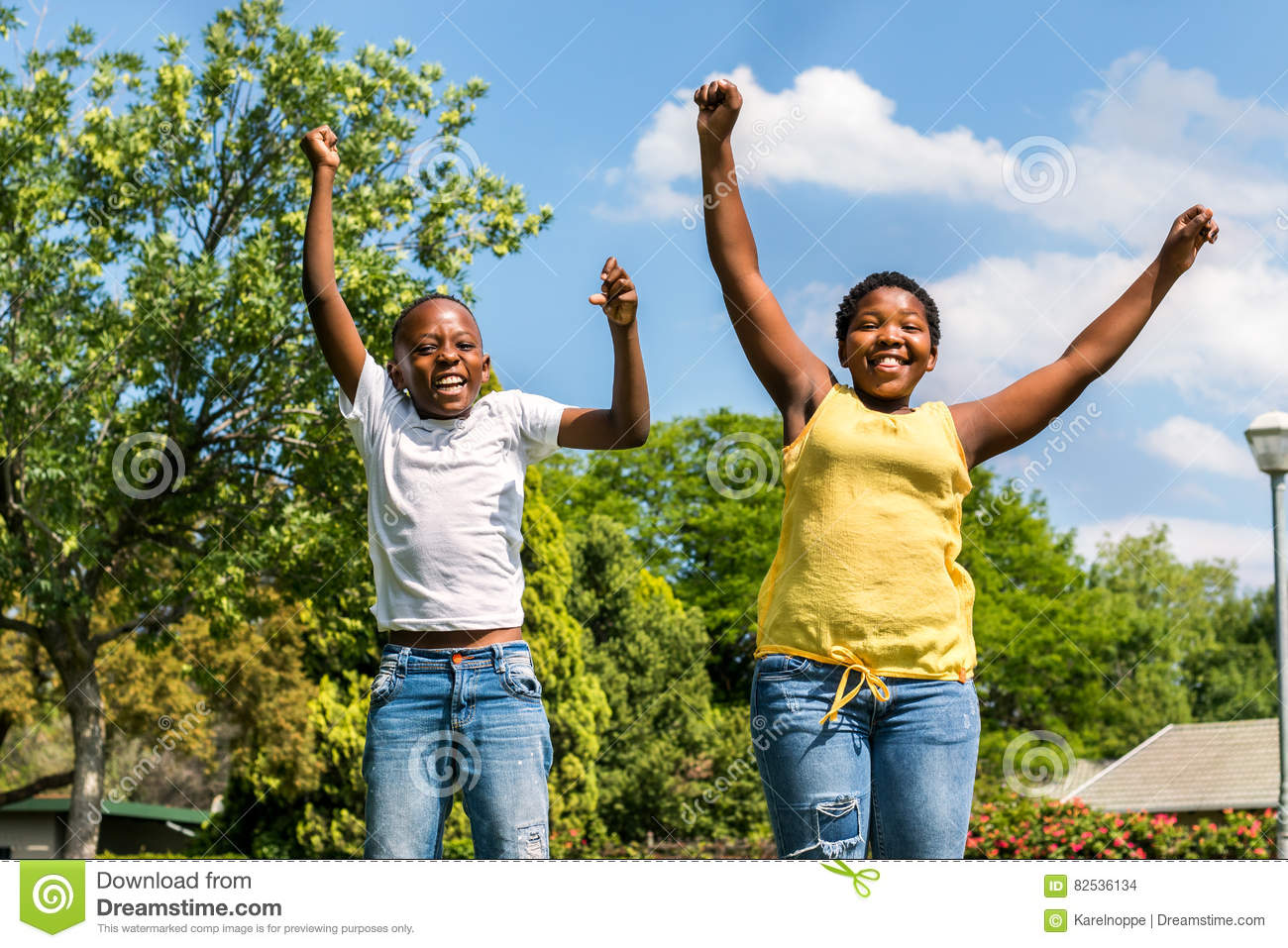 African kids jumping together in backyard.