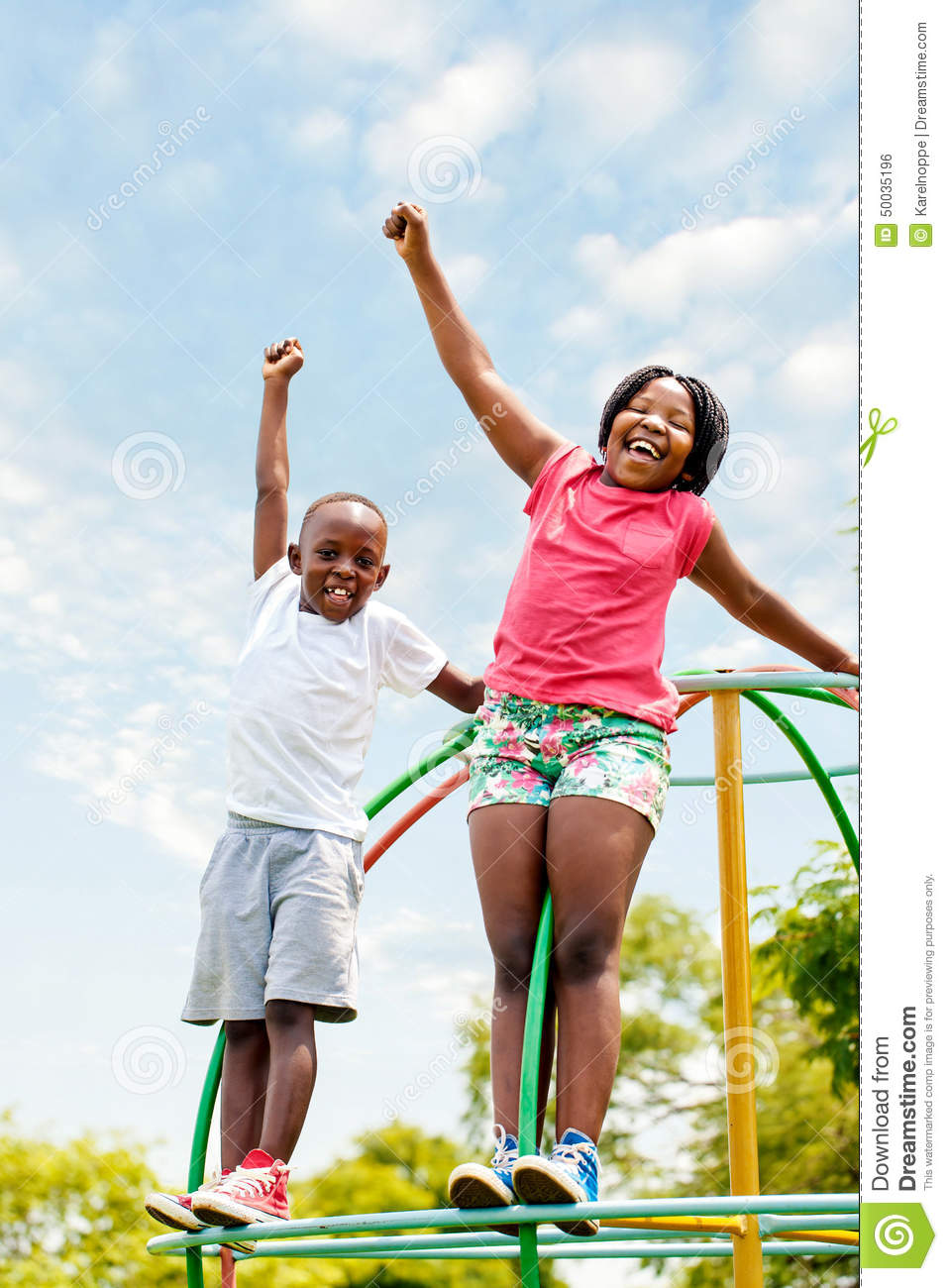 African kids shouting and raising hands in park.