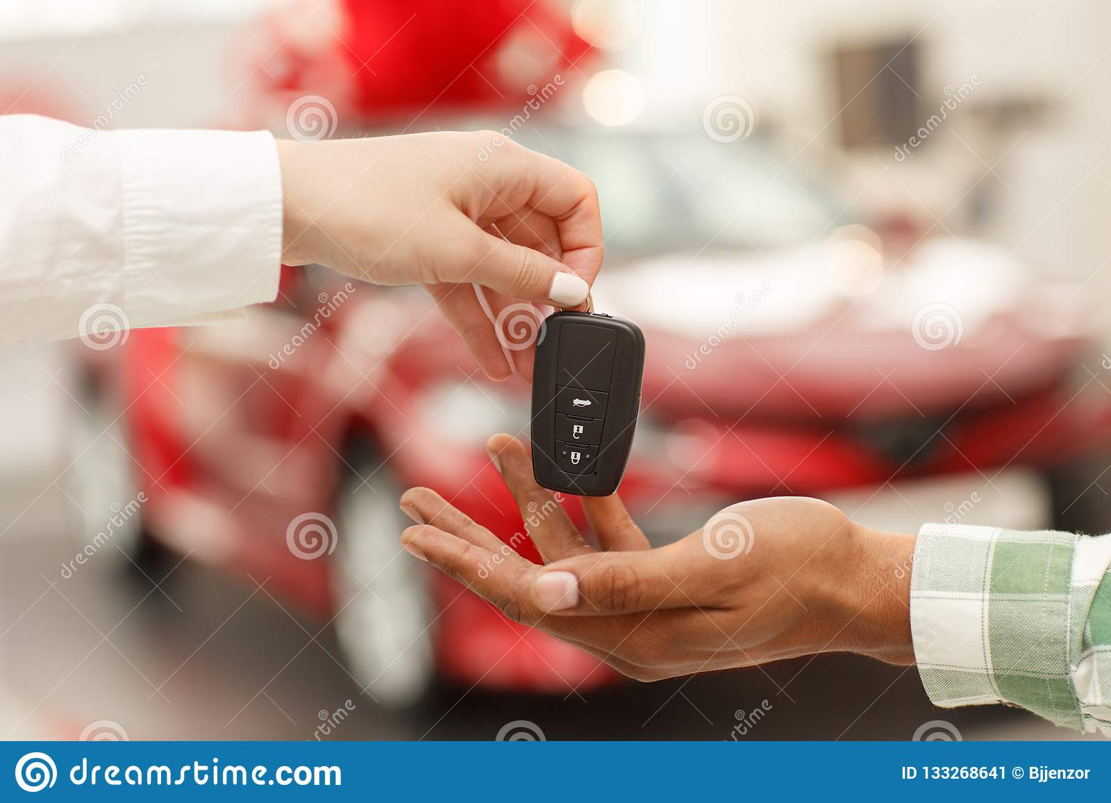 African man receiving car keys from saleswoman