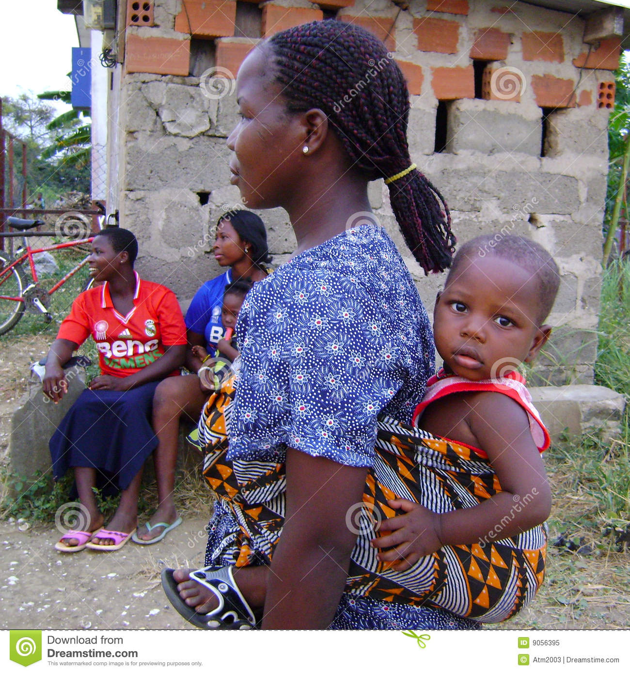african mother with her little baby boy on the back . The photo is ...