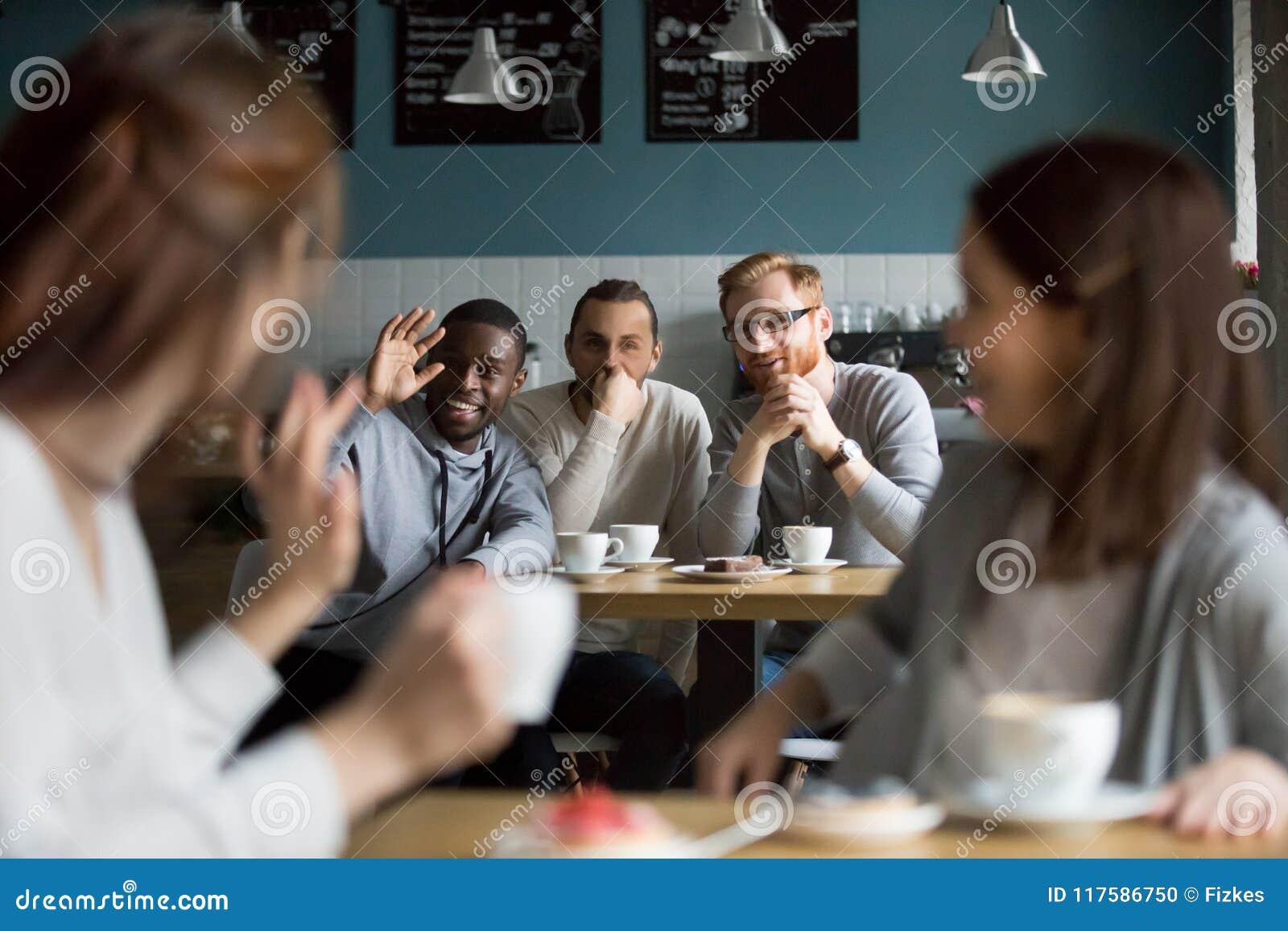 African smiling man waving hand greeting girls meeting in cafe