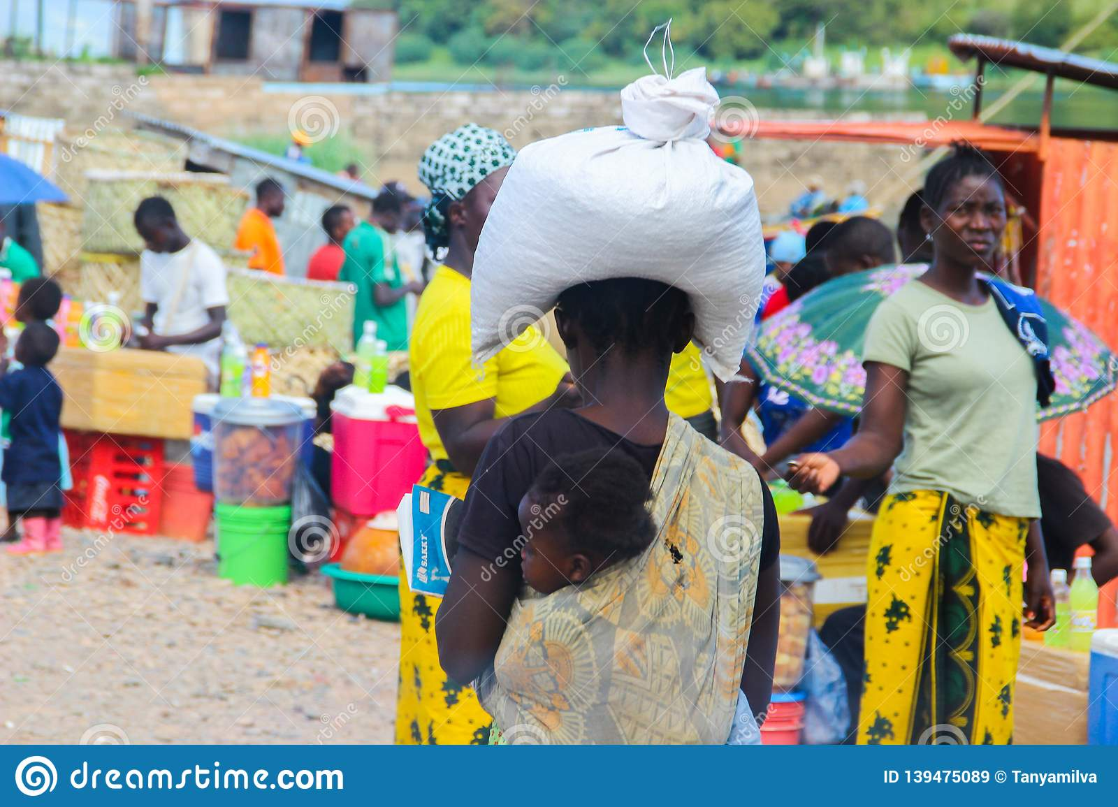 African woman carrying a bag with groceries on her head and a child wrapped in a scarf on her back