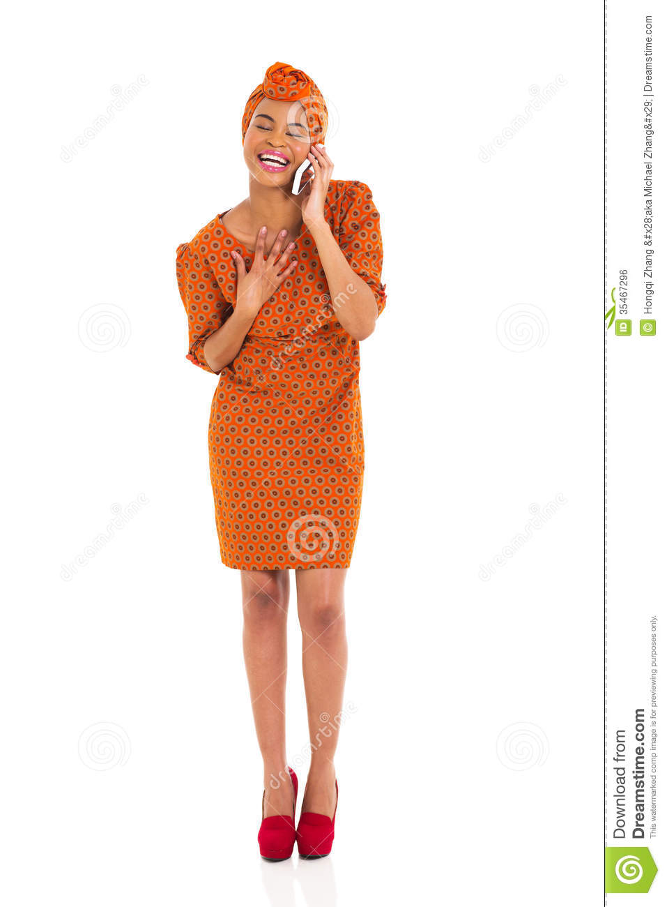 Happy young african woman in traditional attire talking on cell phone.