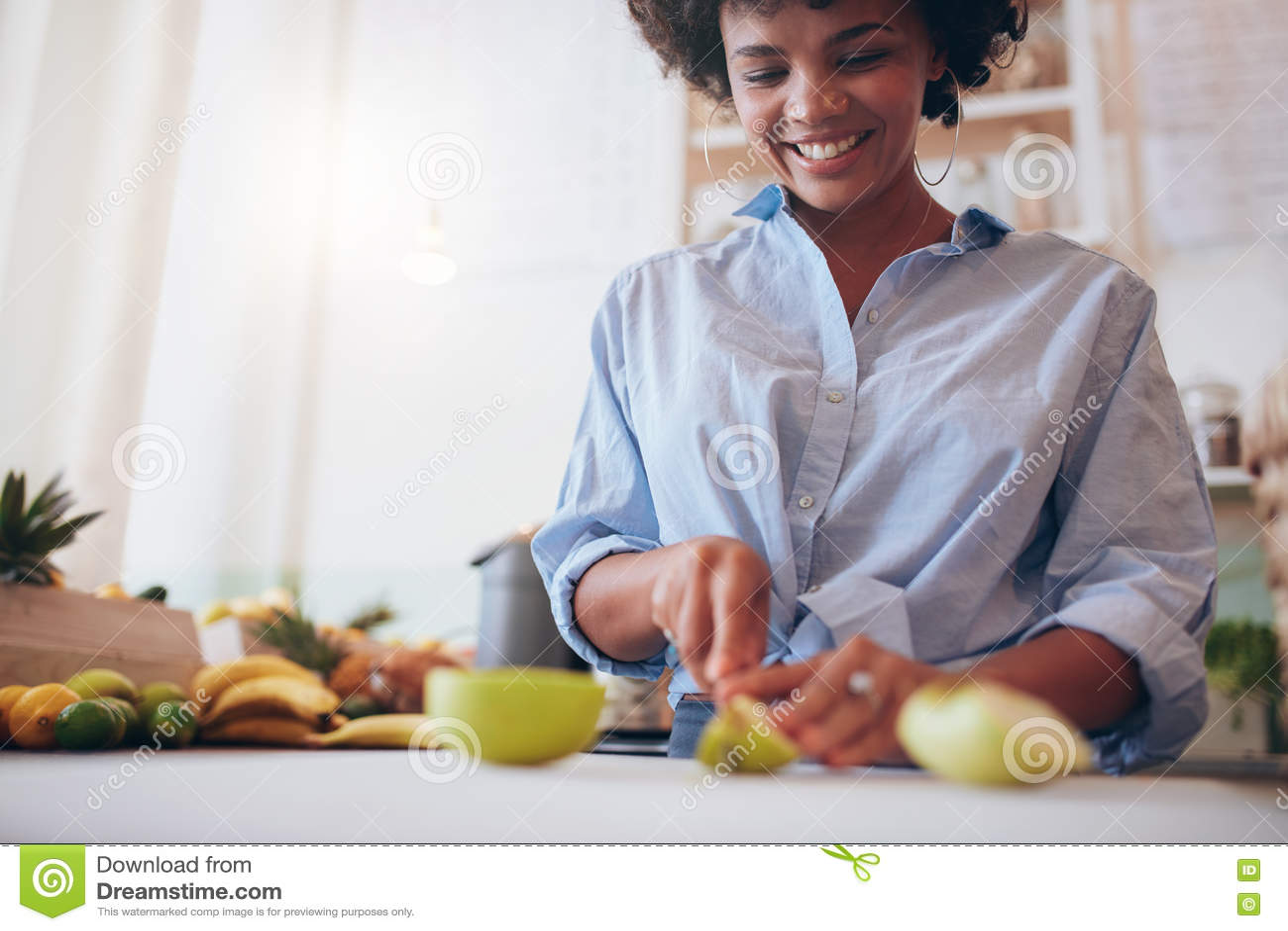 African woman preparing fresh fruit juice