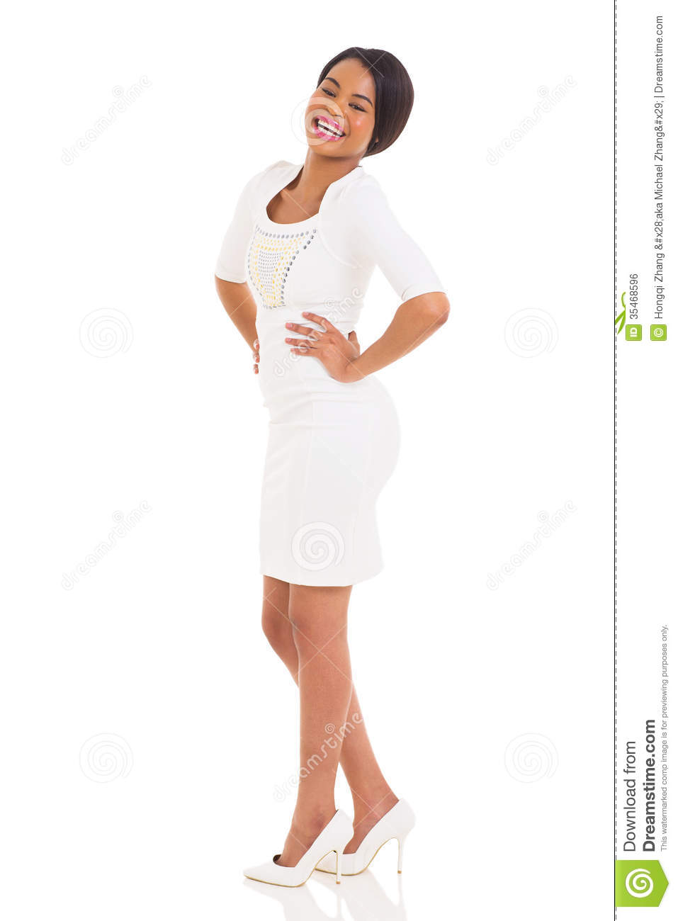 Gorgeous african woman in white dress with her hands on her hips.
