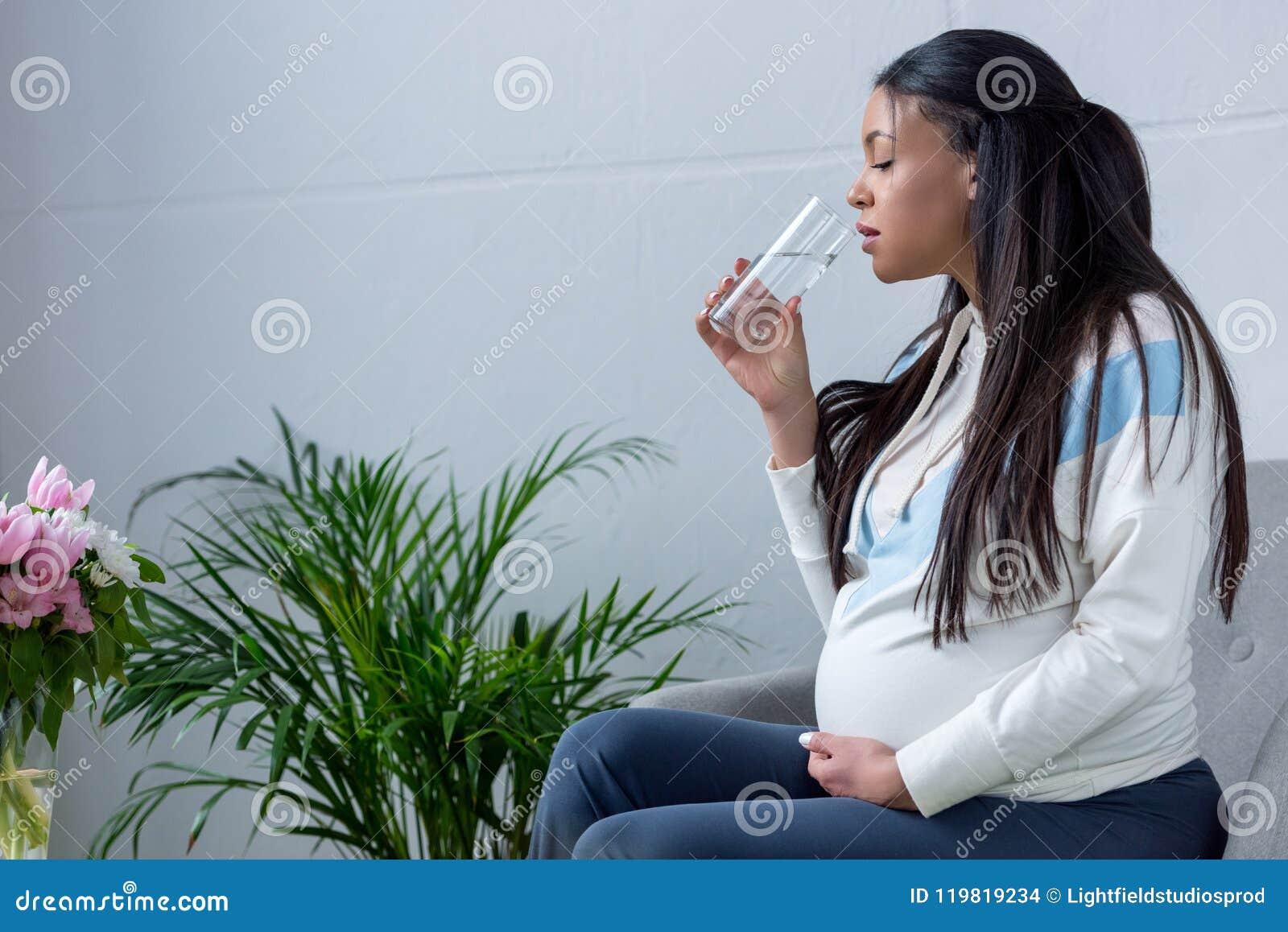 Afrikaans Amerikaans zwanger vrouwen drinkwater terwijl het zitten