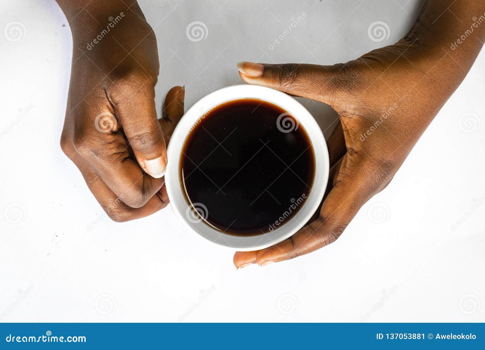 Afrikaanse Amerikaanse vrouw beide handen die een witte kop van koffie houden Zwarte Vrouwelijke handen die een hete kop van koff
