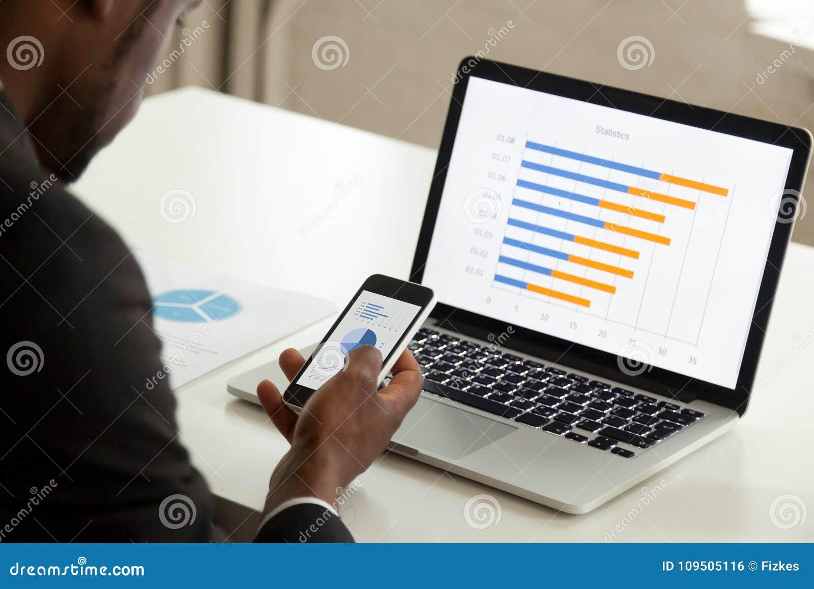 Afrikaanse Amerikaanse zakenman die apparaten voor zaken, over sh met behulp van