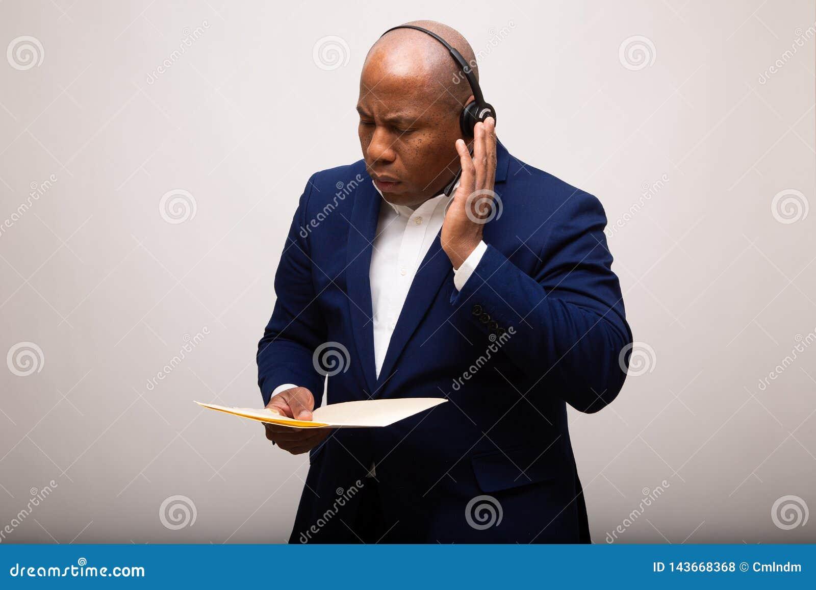 Afrikaanse Amerikaanse Zakenman Listens Through Headset terwijl Bedrijfsdossier