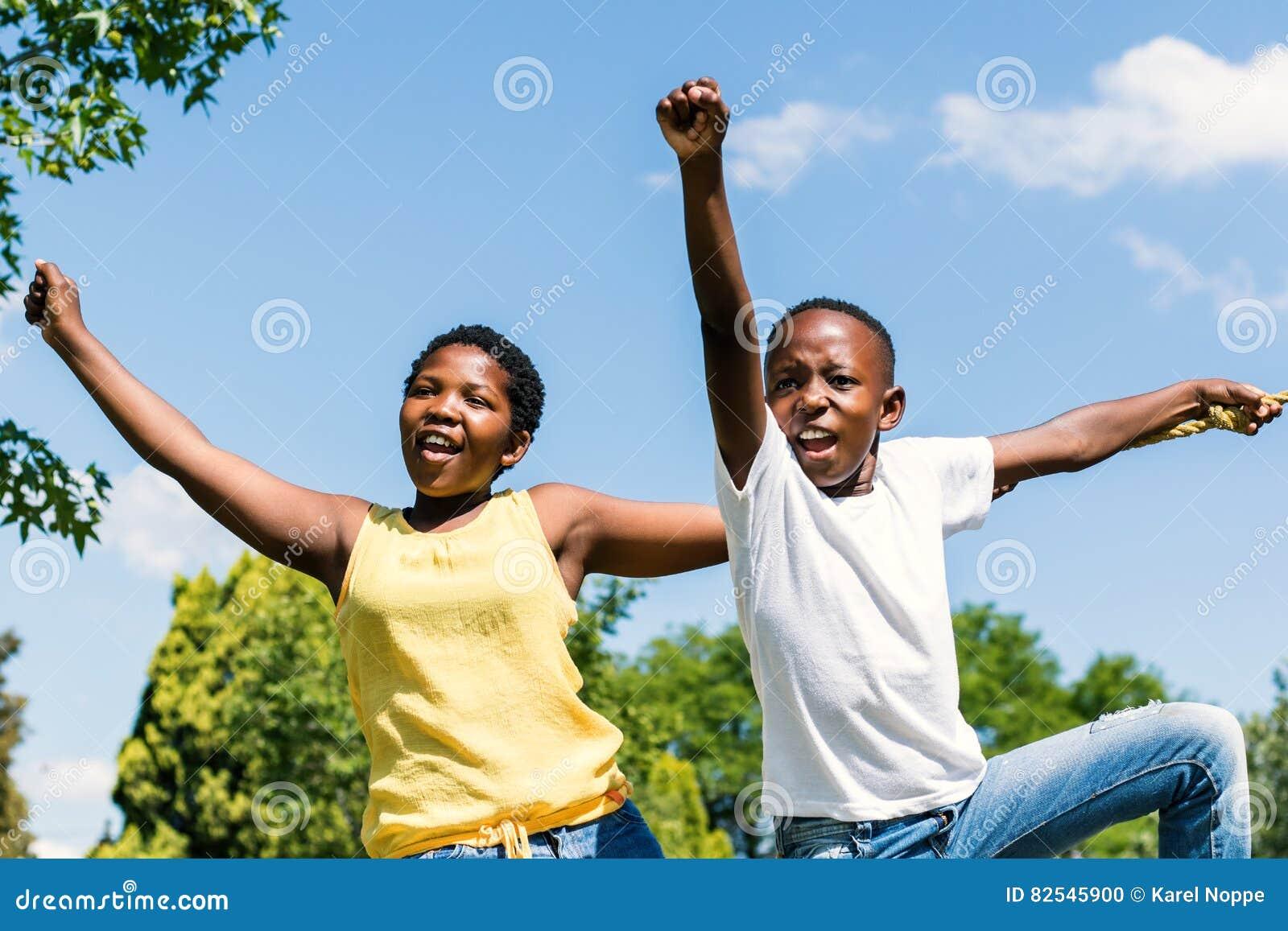 Afrikaanse Jonge geitjes die handen opheffen en in park schreeuwen
