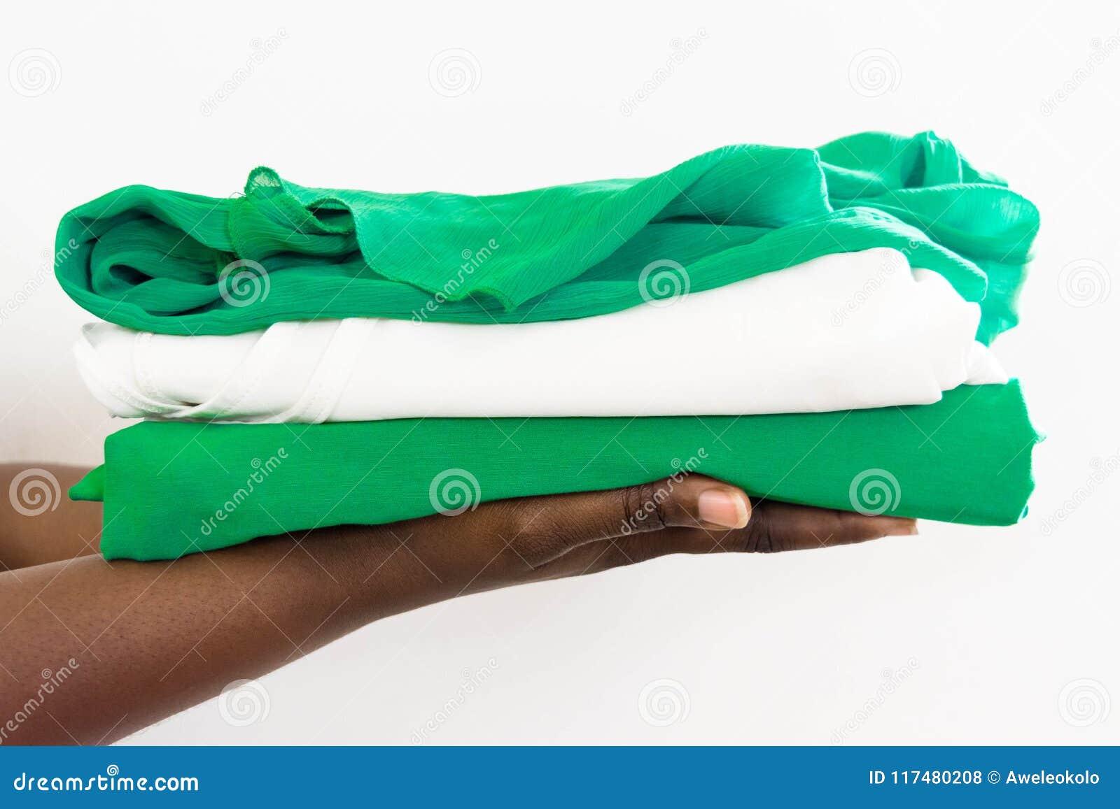 Afrikaanse vrouw die een stapel van kleding in twee handen houden