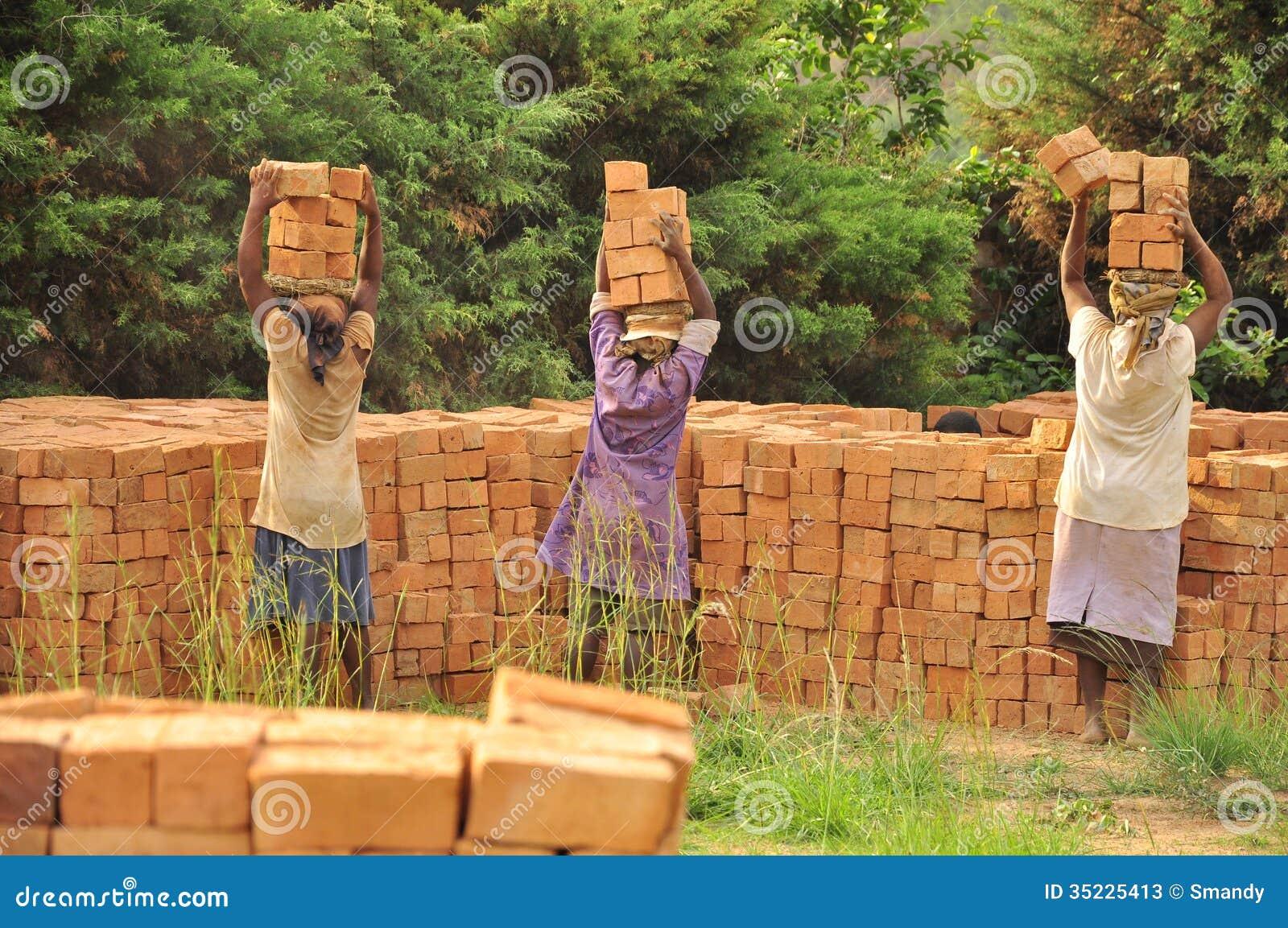 Afrikanerinnen an tragenden Ziegelsteinen der Arbeit