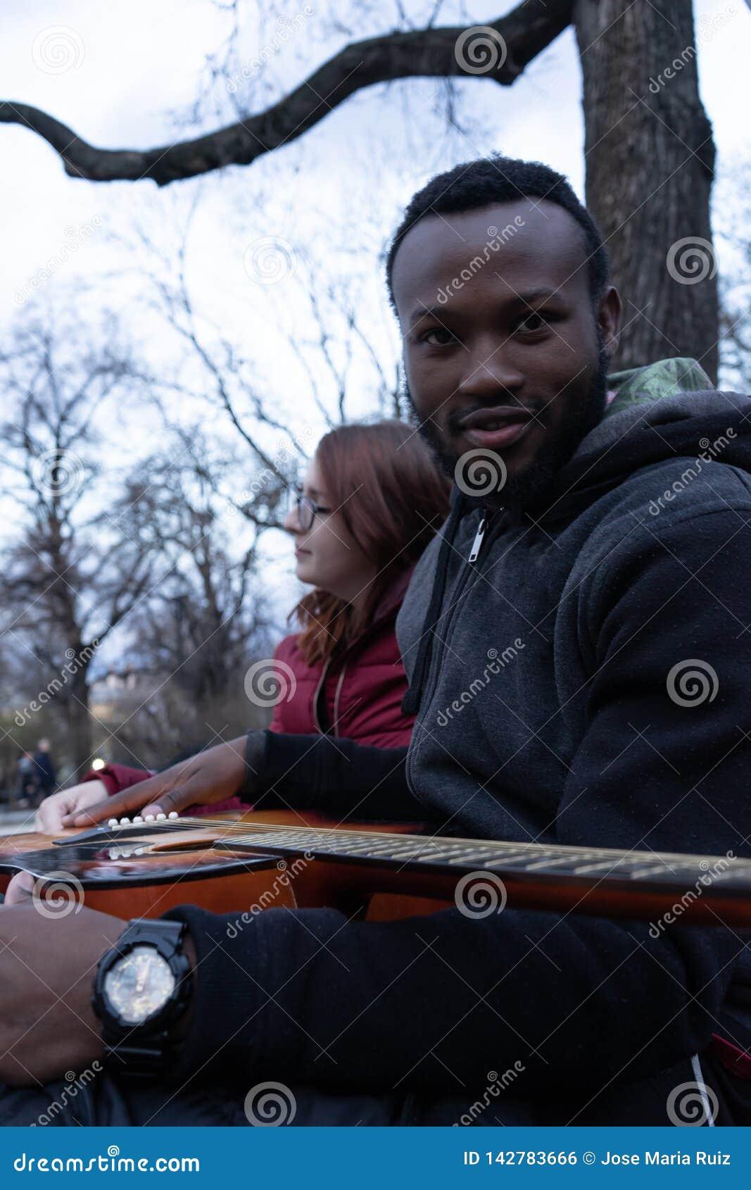 Afrikanischer Kerl mit einer Akustikgitarre und einem weißen Mädchen mit Gläsern im Park