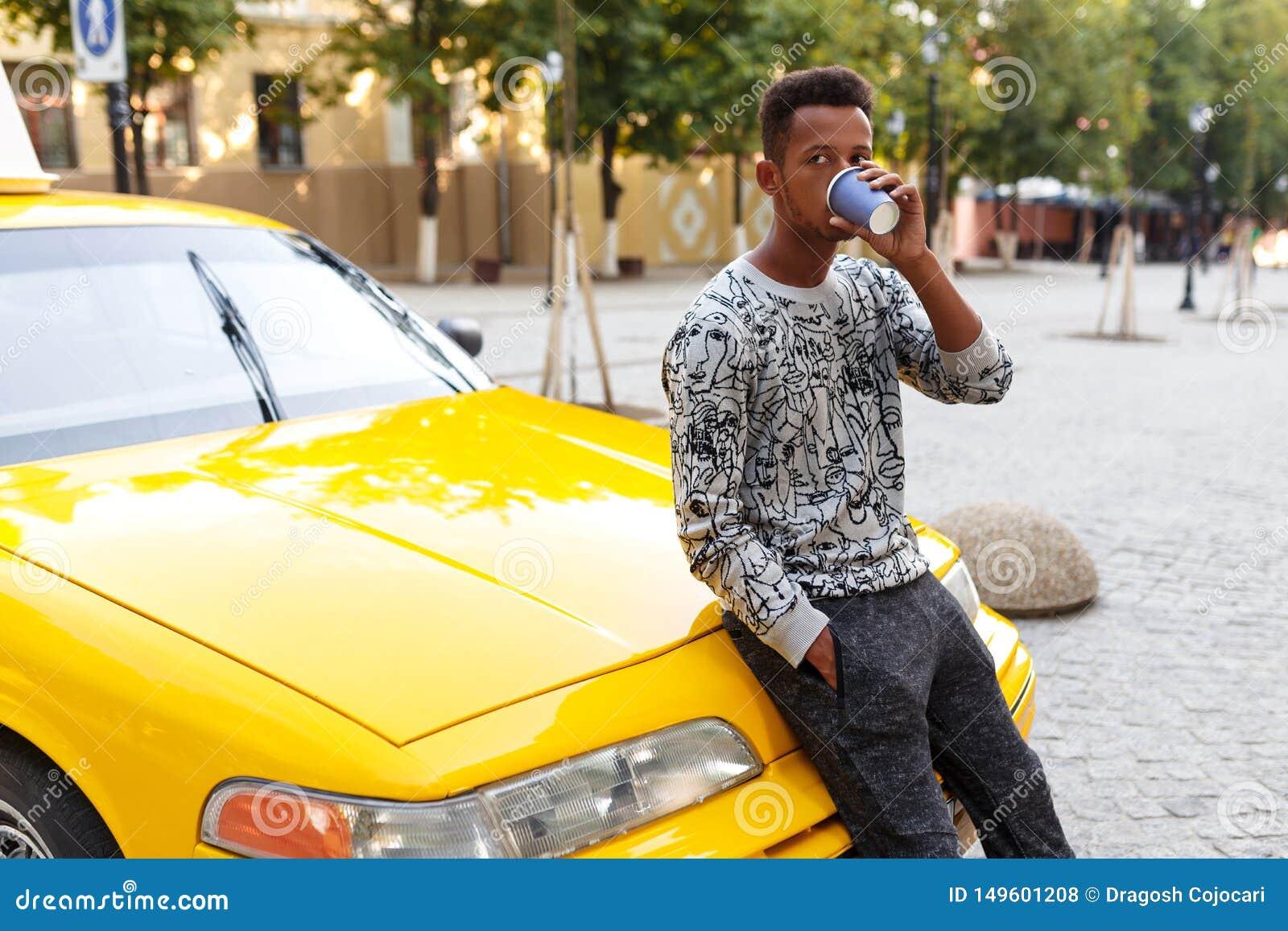 Afrikanischer Mann, der einen Kaffee gesetzt auf der Haube eines Taxis, schauend zu einer Seite, auf einem Stra?enhintergrund tri