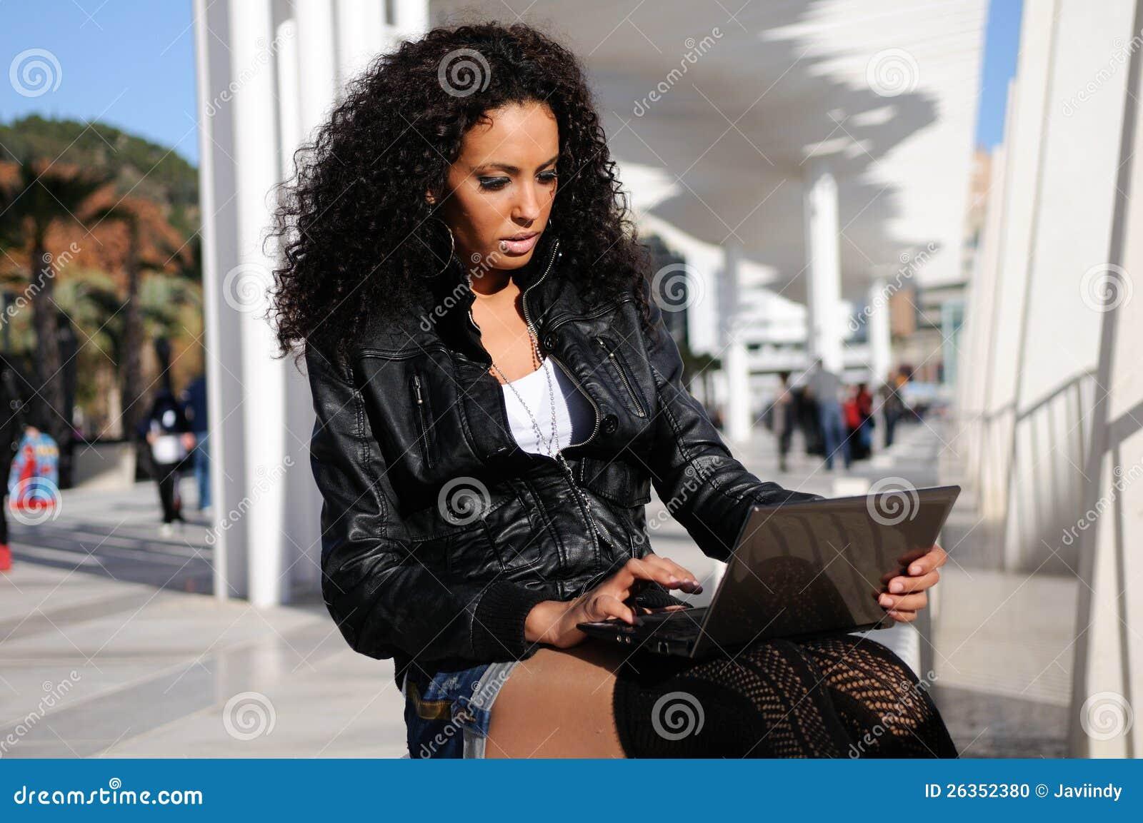 Afrikanisches Mädchen, das einen Laptop in der Straße verwendet